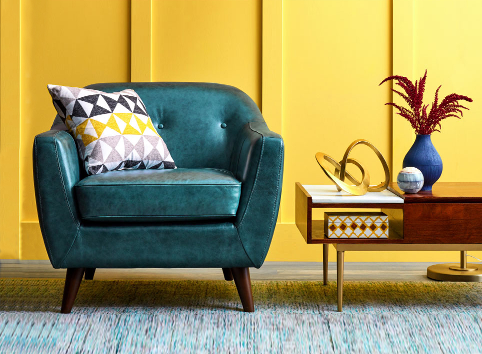 Best Things to Buy at HomeGoods, teal chair, decorative pillow, vase, sculpture, and yellow wall