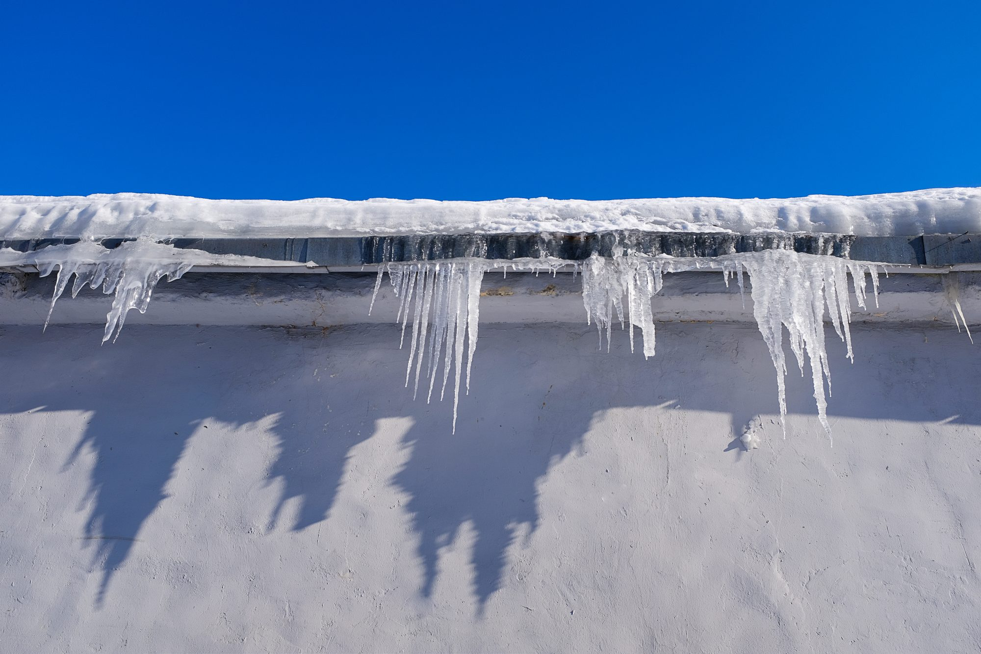 keep-pipes-from-freezing-cold-weather: roof line with icicles