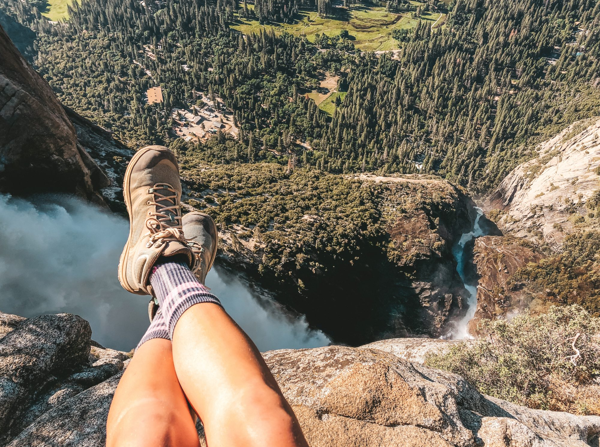 how-to-choose-hiking-boots: woman on a cliff wearing hiking boots