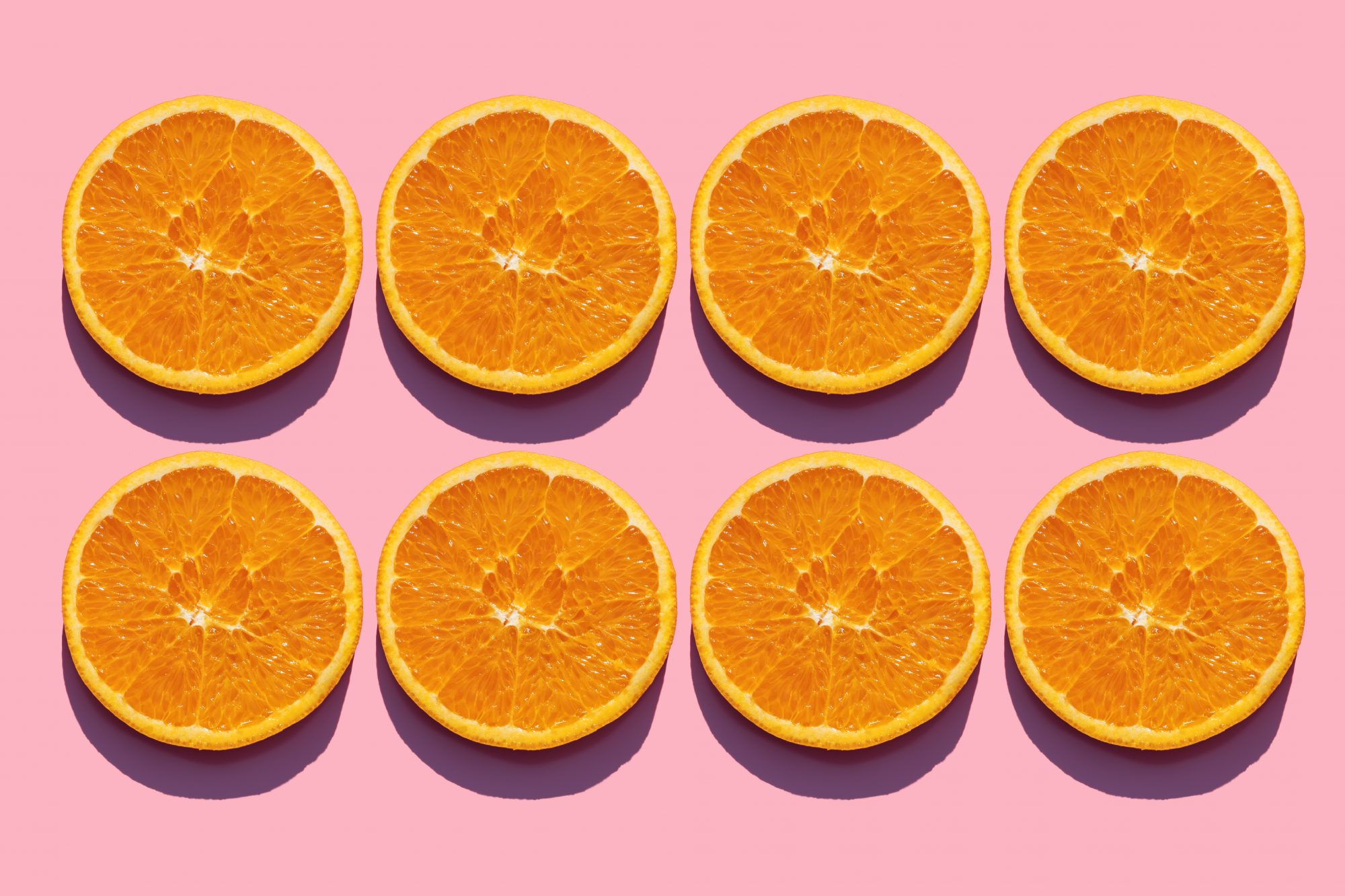 orange-benefits: slices of orange on a pink background