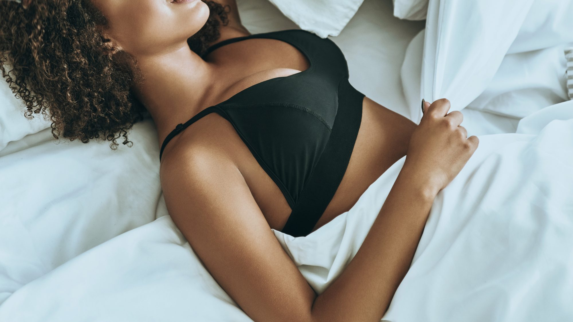 Do You Wear a Bra to Sleep? Here's What to Avoid Wearing: women sleeping in bed with a bra on