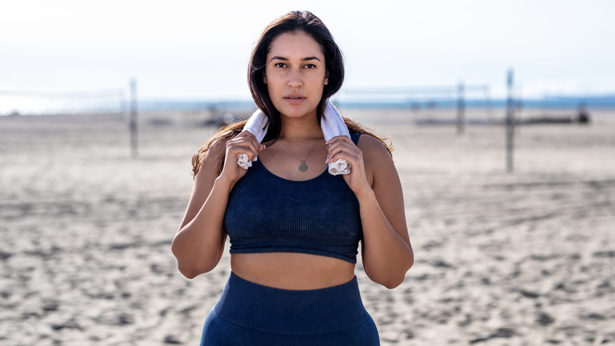 What Happens When You Wear a Sports Bra All Day Every Day: woman wearing a sports bra at the beach