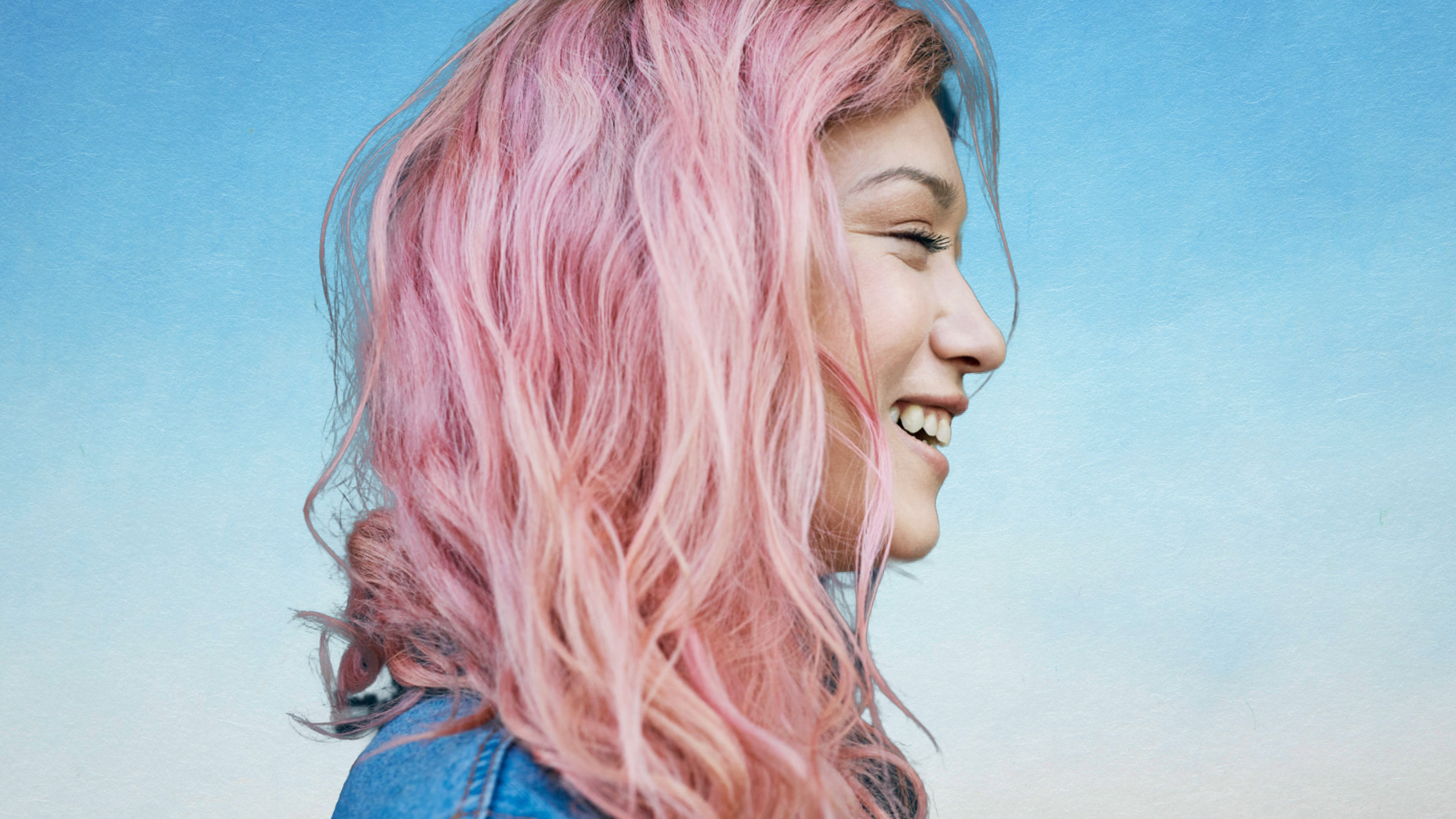 best-products-for-color-treated-hair: woman with pink hair laughing