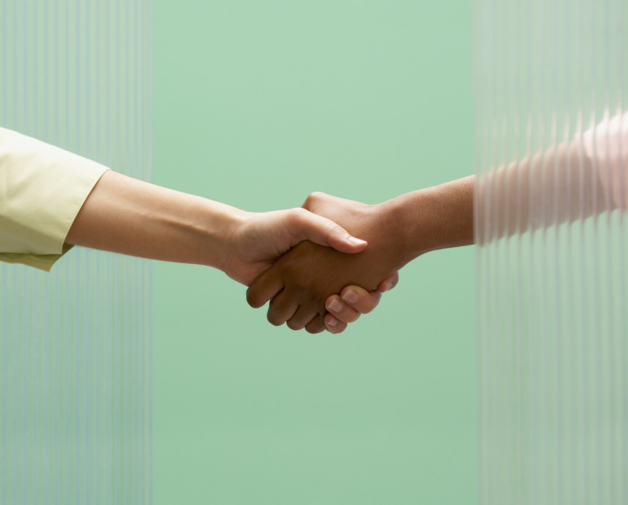 How to Follow Up After a Job Interview: two people shaking hands on a green background