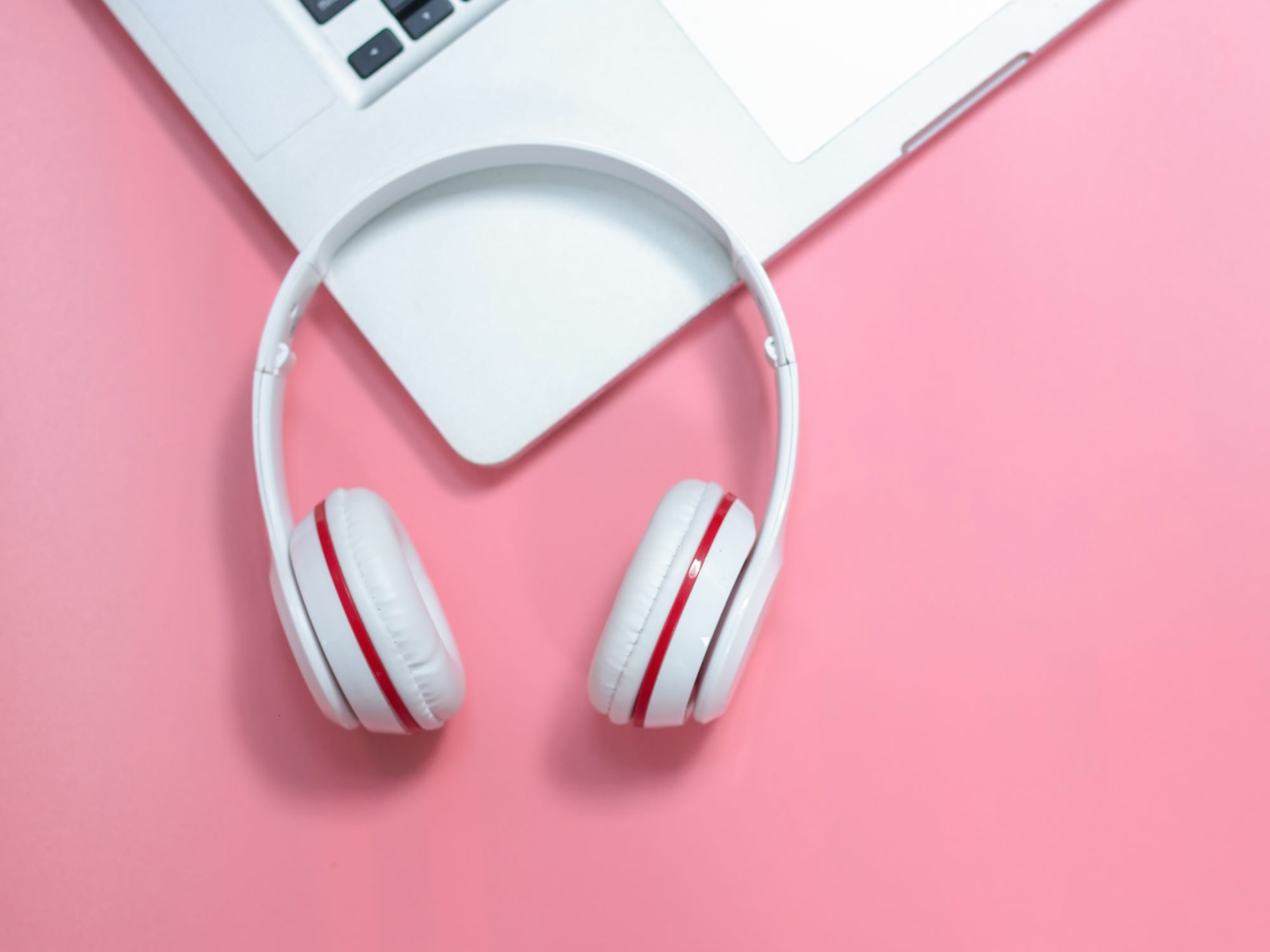 Podcasts to Listen to While Working: headphones and keyboard on a pink background