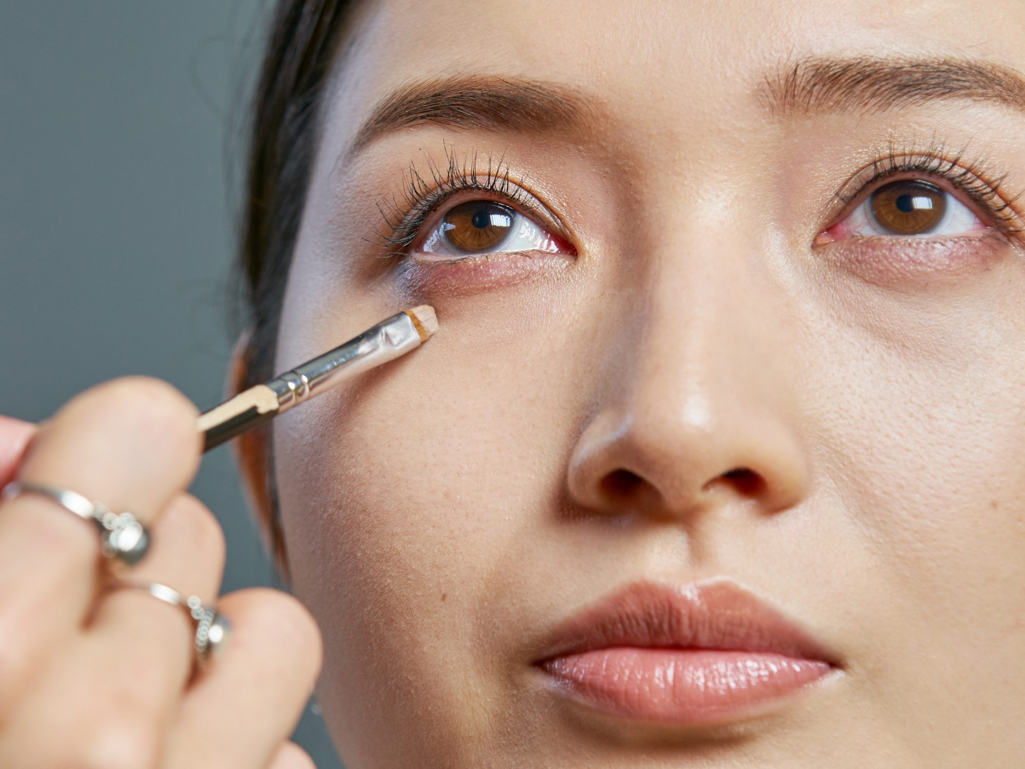 how-to-color-correct-undereye-circles: makeup artist applying concealer under a woman's eyes