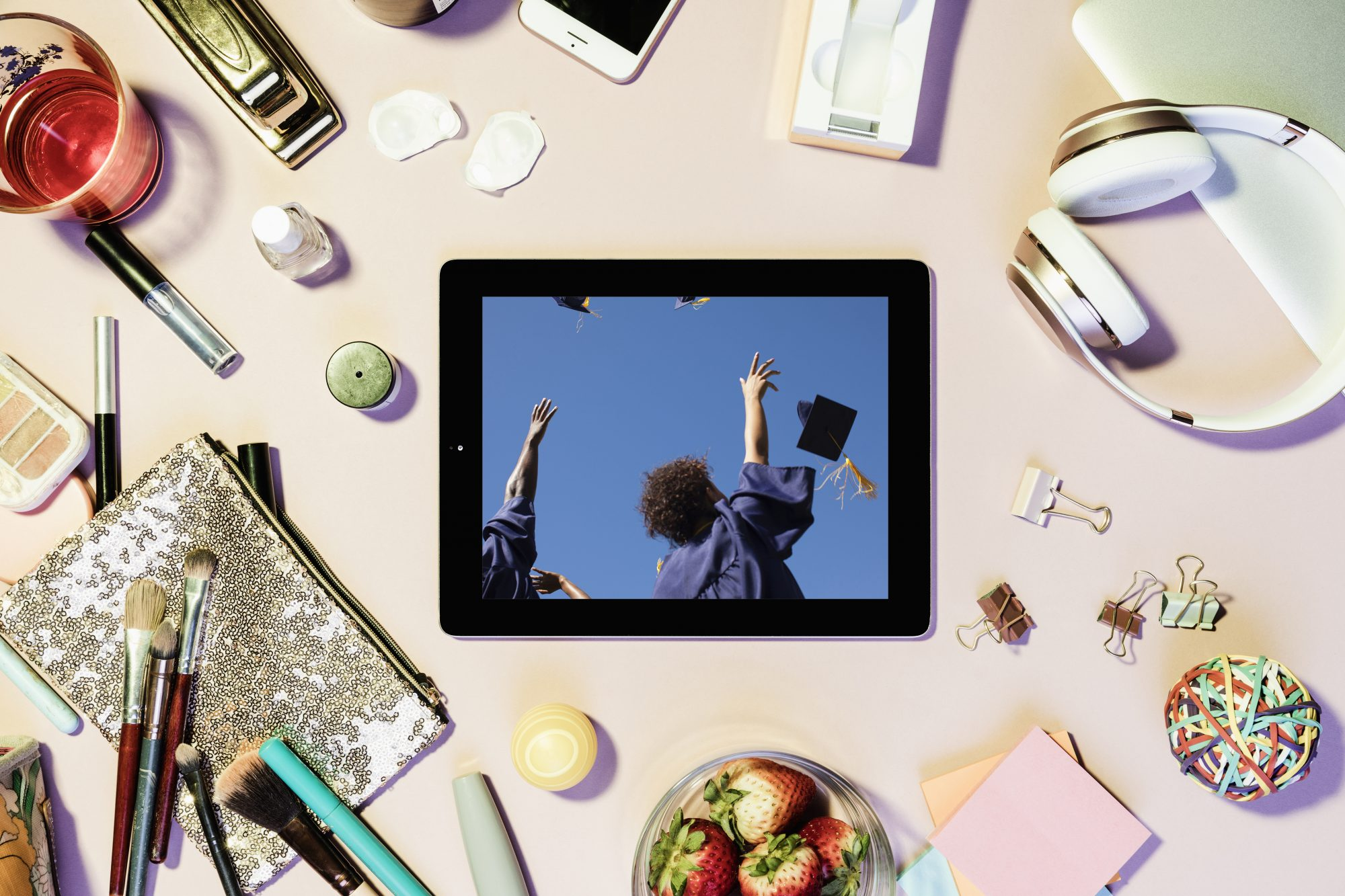 Tips for Navigating the Shift From College Student to Working Adult: tablet with image of graduation ceremony