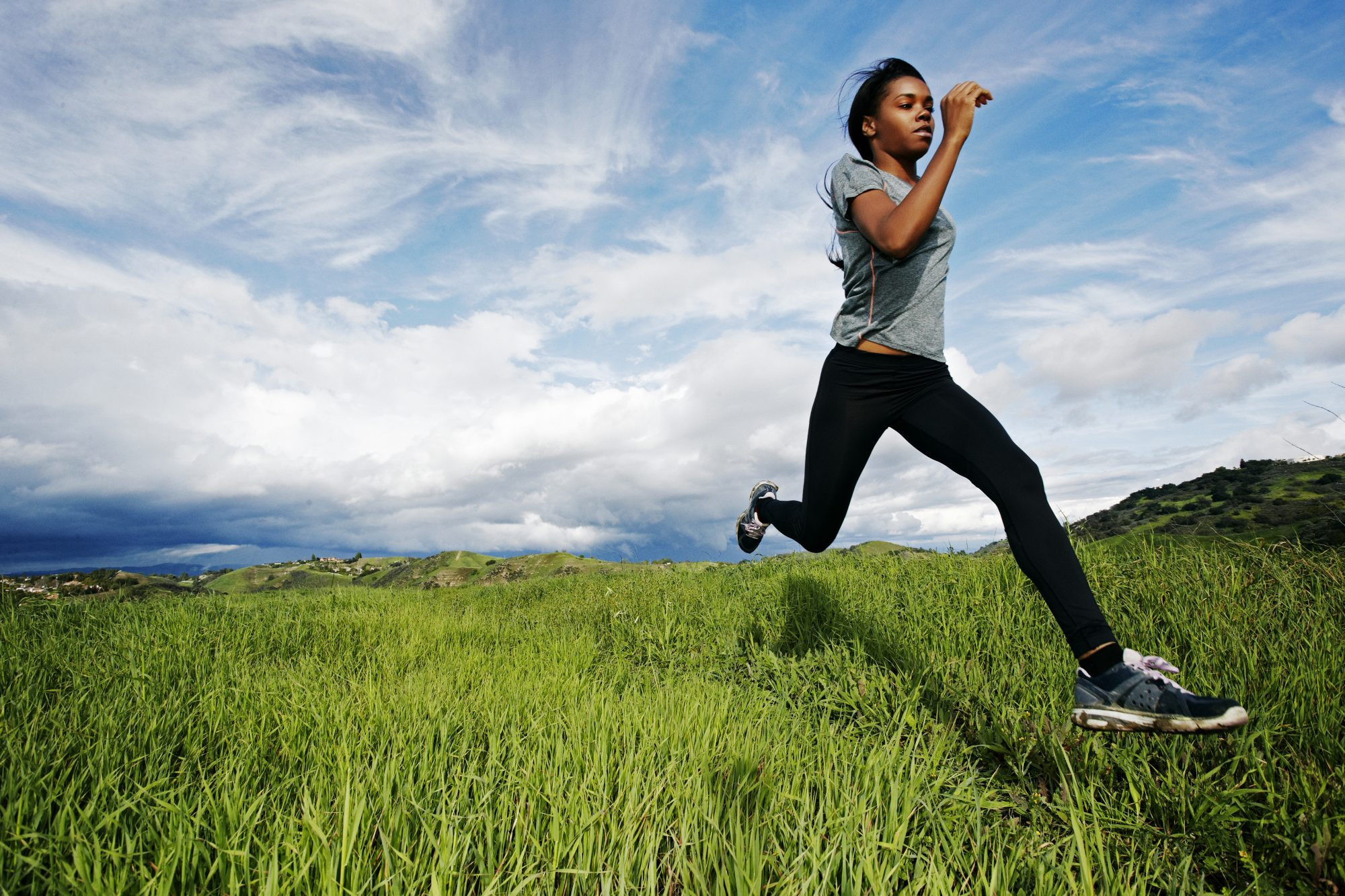 Mindful Running tips - how to practice mindful running: woman running in a grassy field