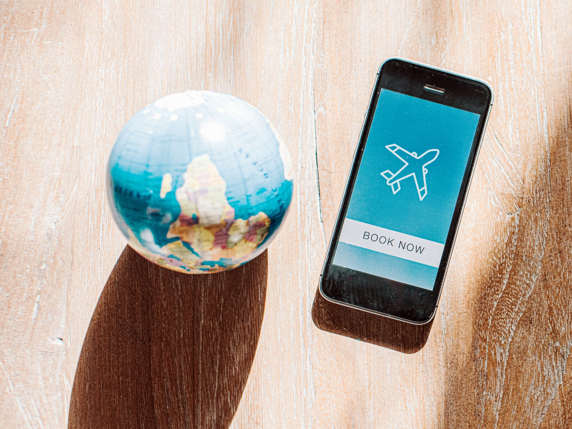 flight-booking-sites-apps: cellphone and globe