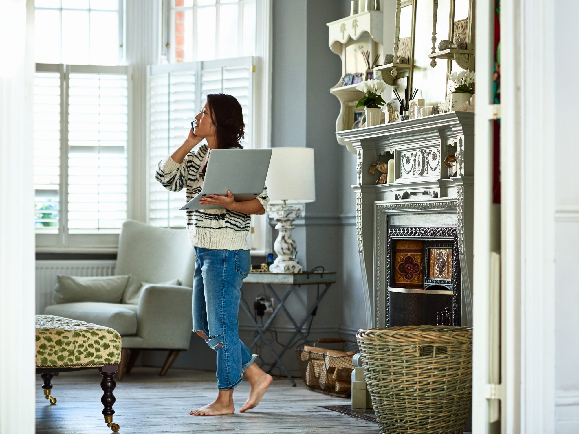 working-from-home-permanently: woman holding a laptop and talking on the phone at home
