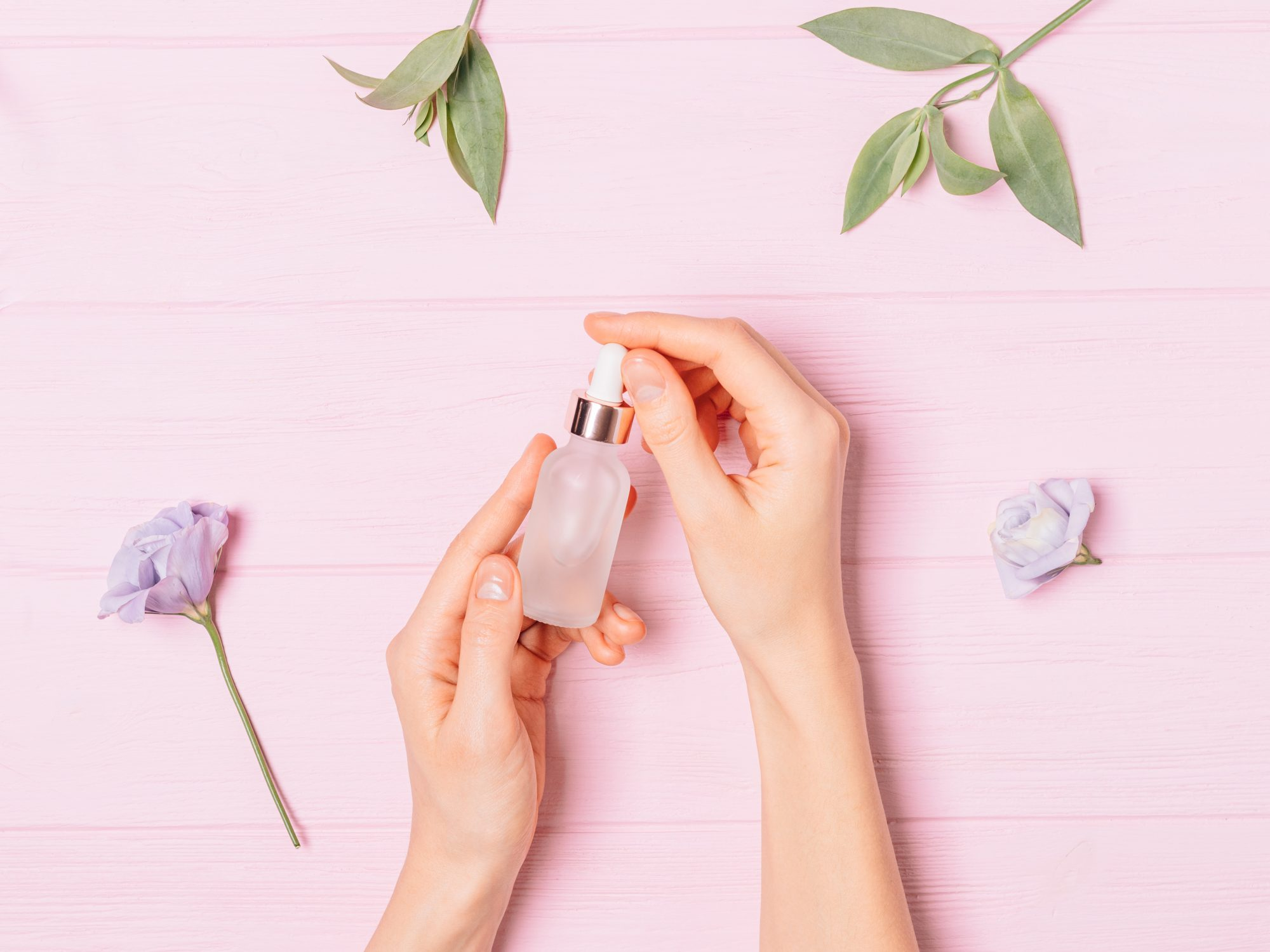 how-to-apply-retinol-in-summer: woman holding bottle of serum