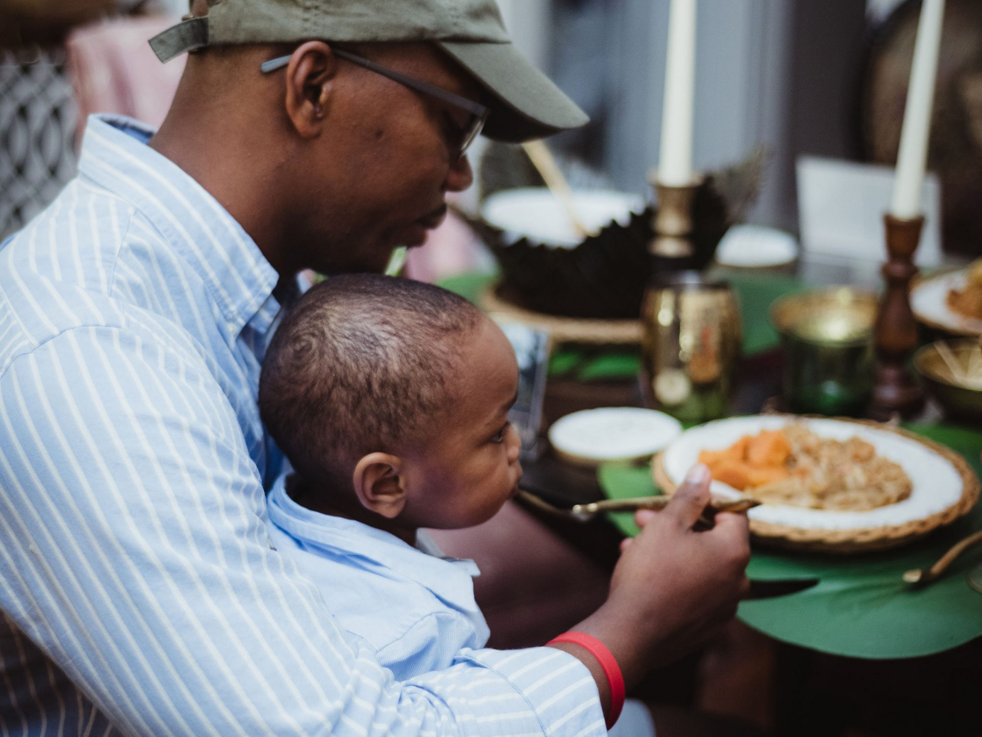 Photo of a child sitting on a man's lap at a Juneteenth celebration meal