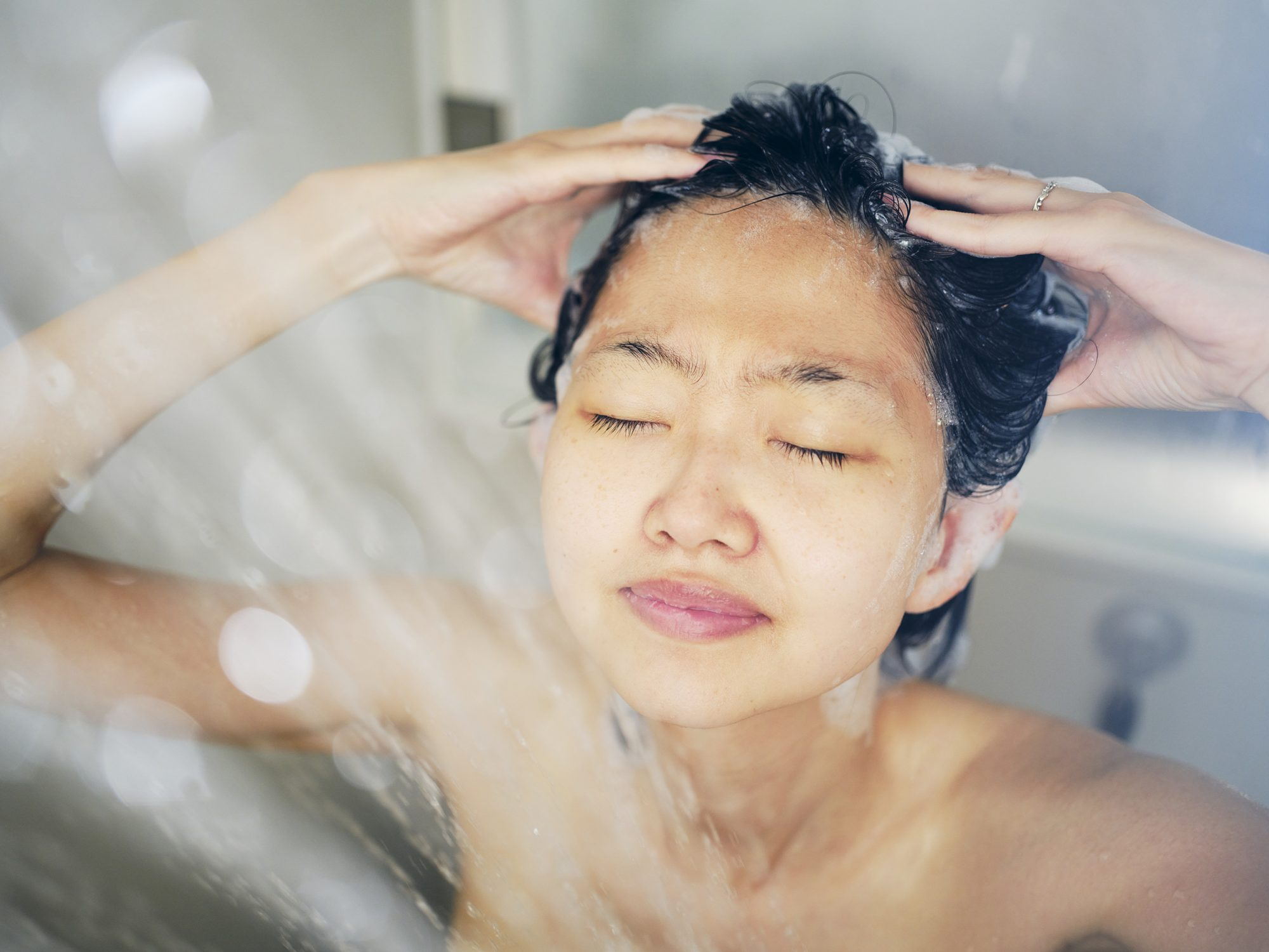 do-2-in-1-haircare-products-work: woman washing hair in shower