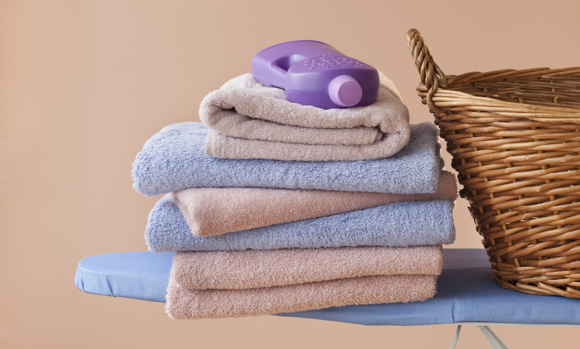 how-often-to-wash-towels: stack of folded towels and laundry basket