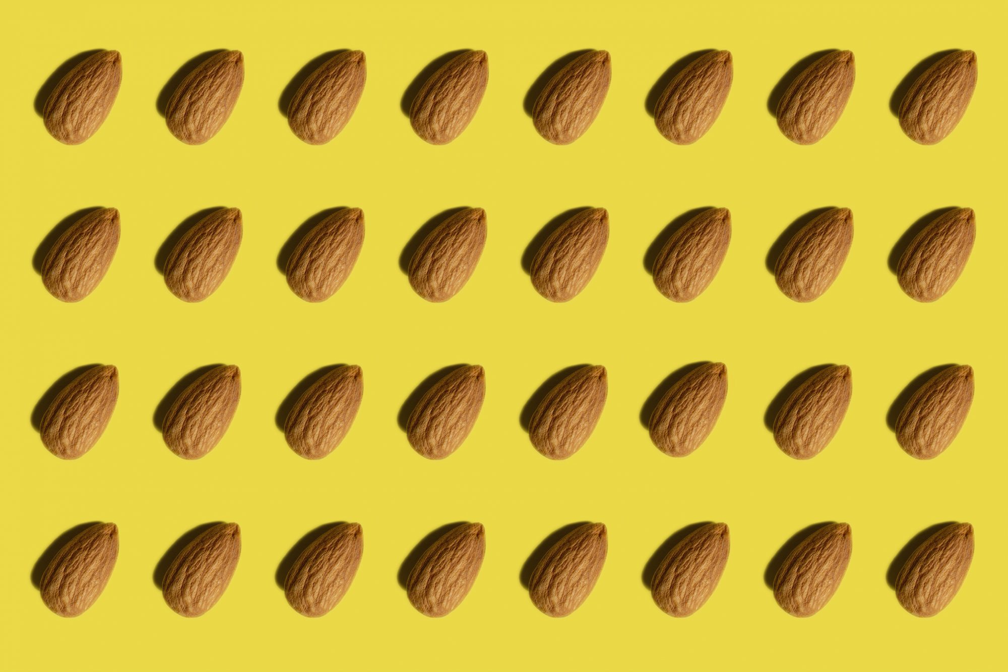 Should You Take a Food Sensitivity Test? Experts Weigh In: Full frame shot of many almonds On Yellow Background And One Capsule