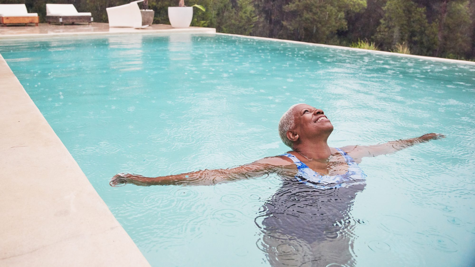 What Does Longevity Mean? How to Live a Longer, Happier, Healthier Life: A mature woman relaxes in a swimming pool o a rainy day