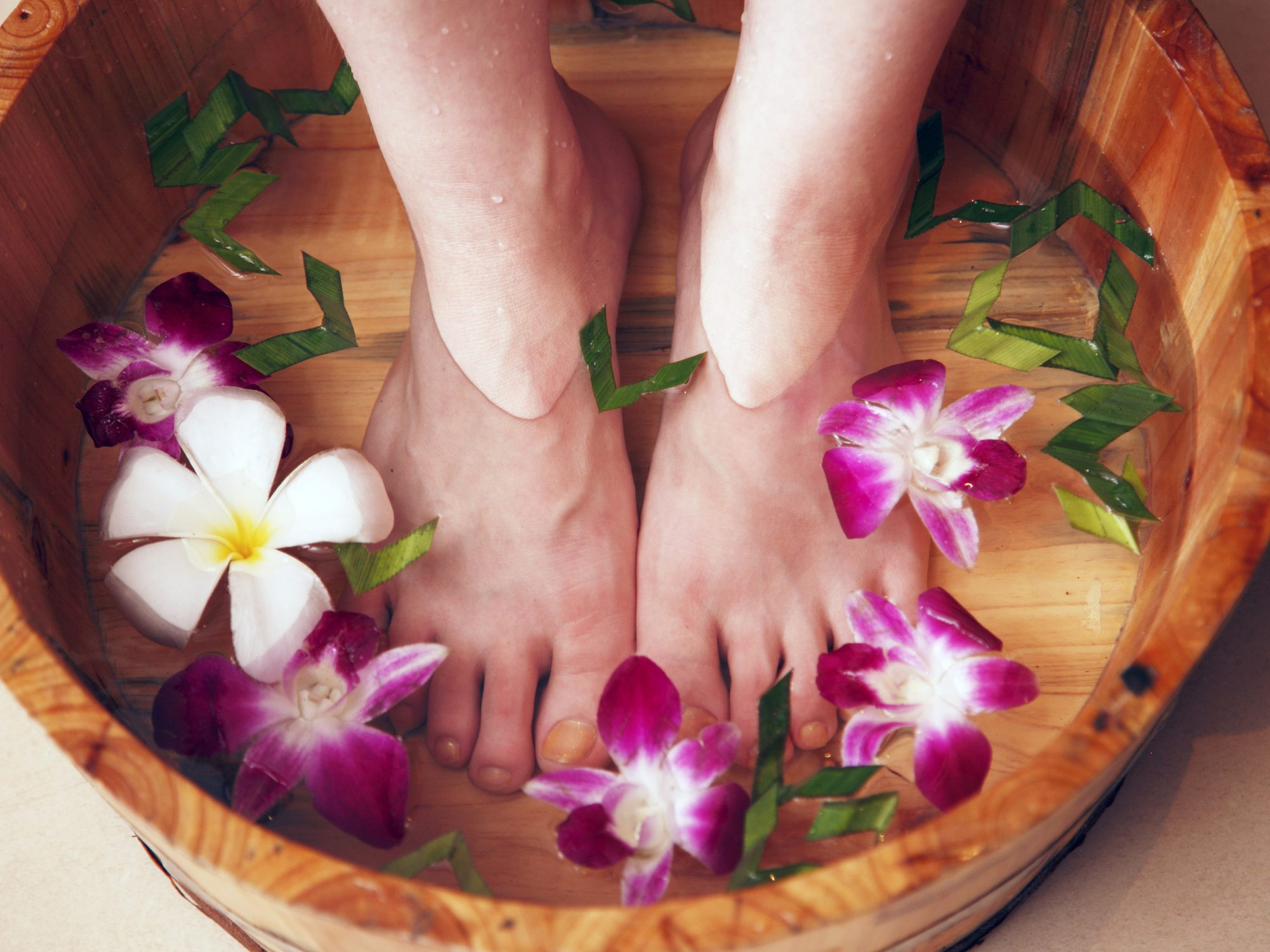 Why Your Feet Hurt: Common Causes of Foot Pain. closeup shot of woman soaking her feet in water