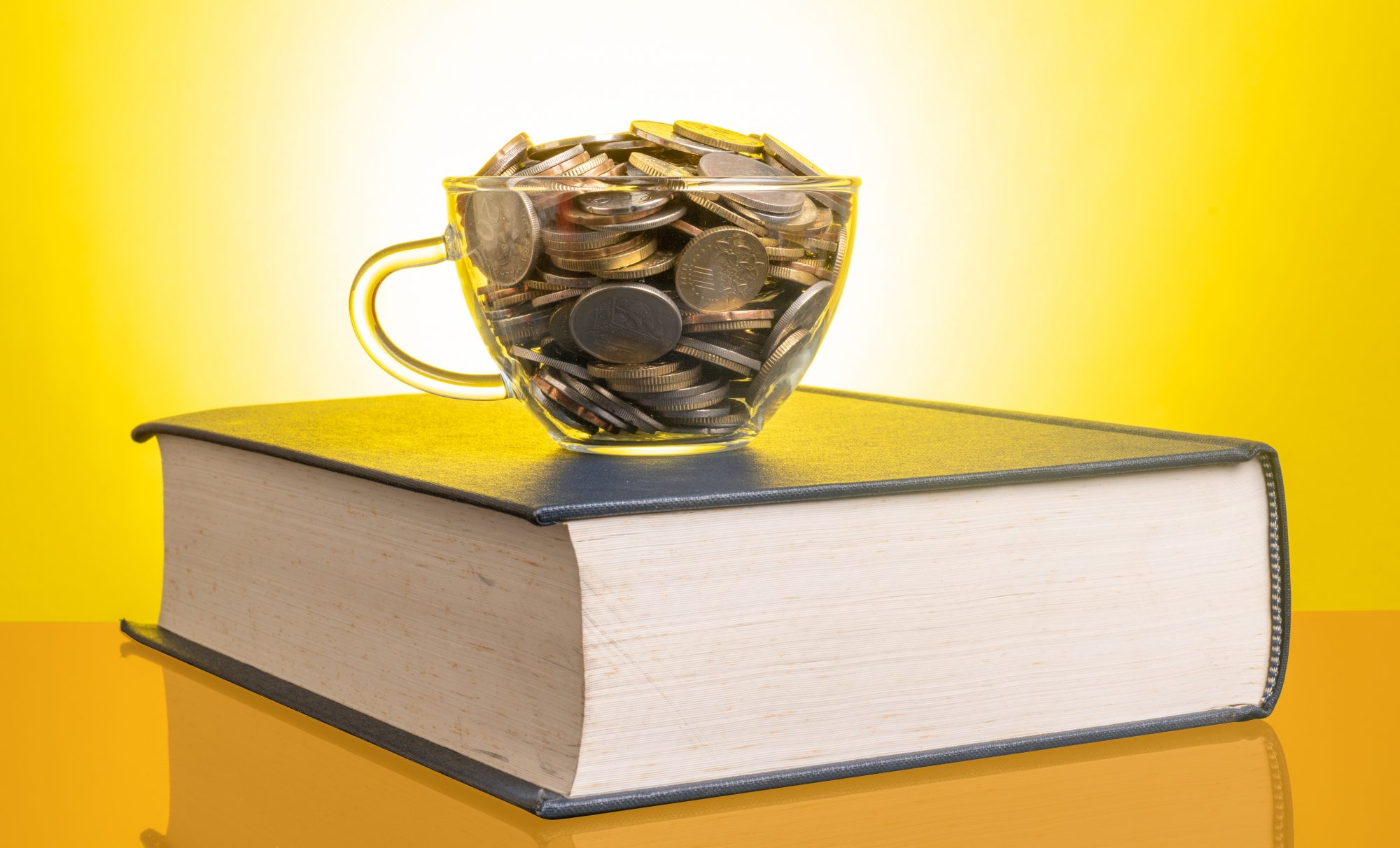 save-money-on-college-tuition: text book and coins