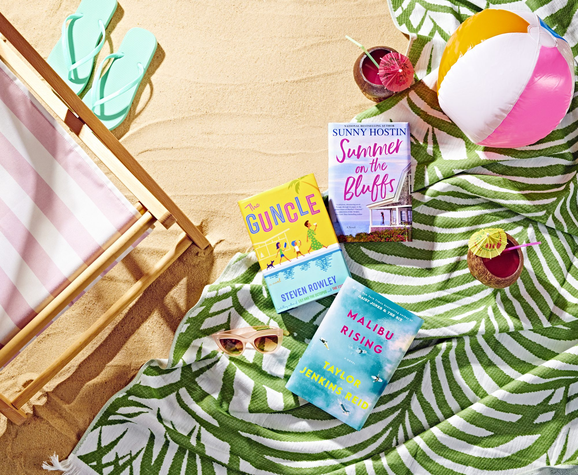 three books laying on towel at the beach, surrounded by a beach chair, flip flops, inflatable ball, and drinks: best beach reads 2021