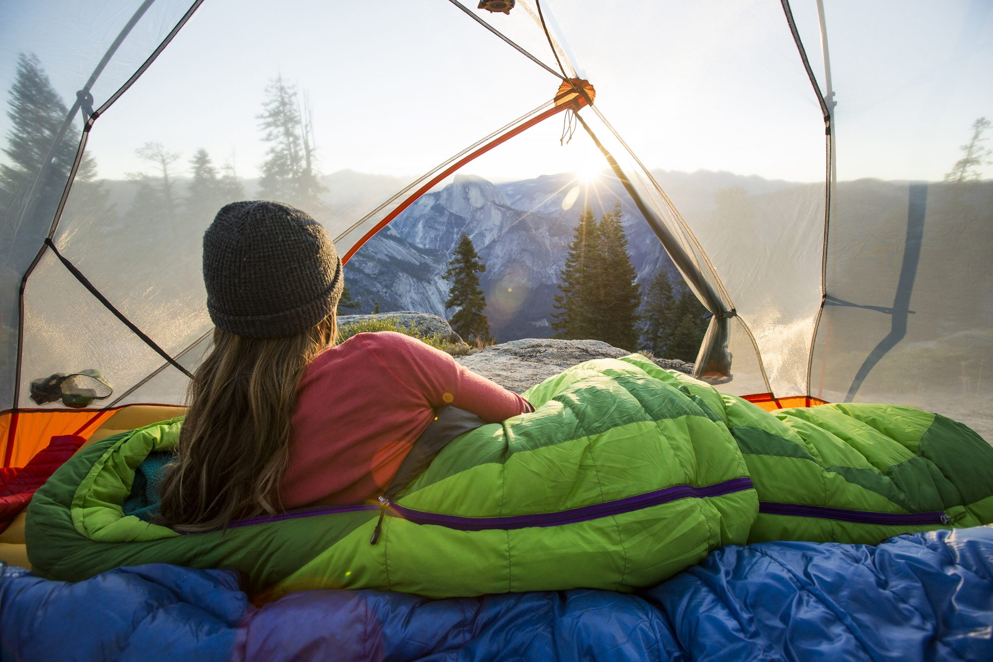 U.S. Campgrounds to Visit With Friends Family or Solo: woman lying in a sleeping bag in a tent