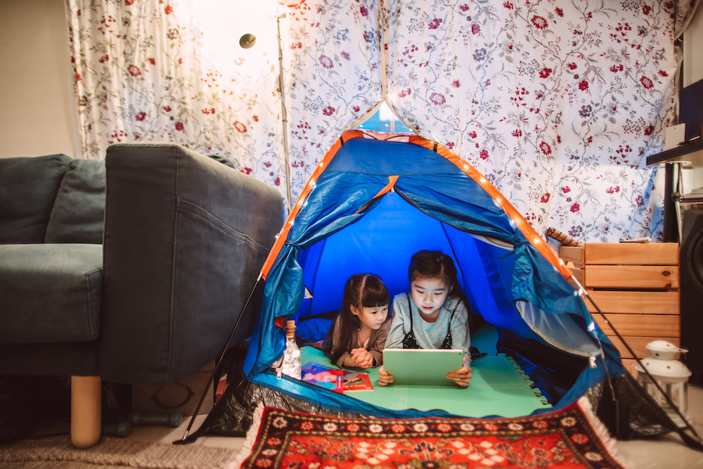 Two Kids indoor camping in a tent