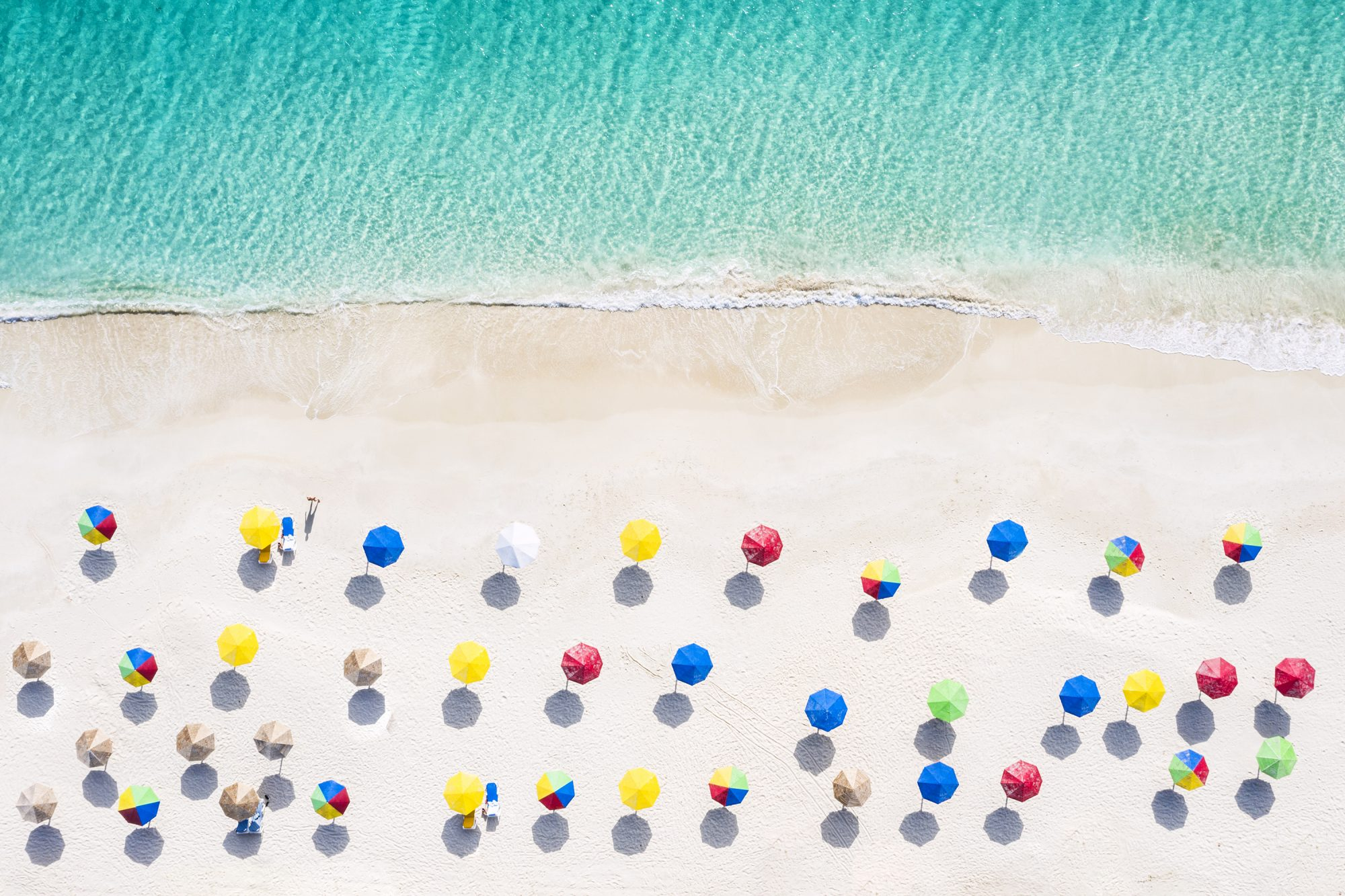 affordable-beach-towns: aerial shot of beach with colorful umbrellas