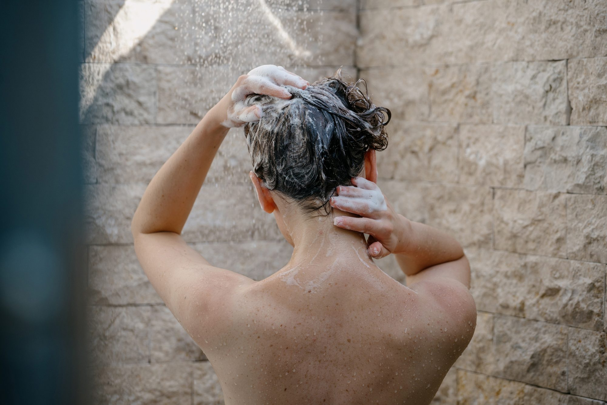 how-to-wash-hair: woman washing hair in the shower