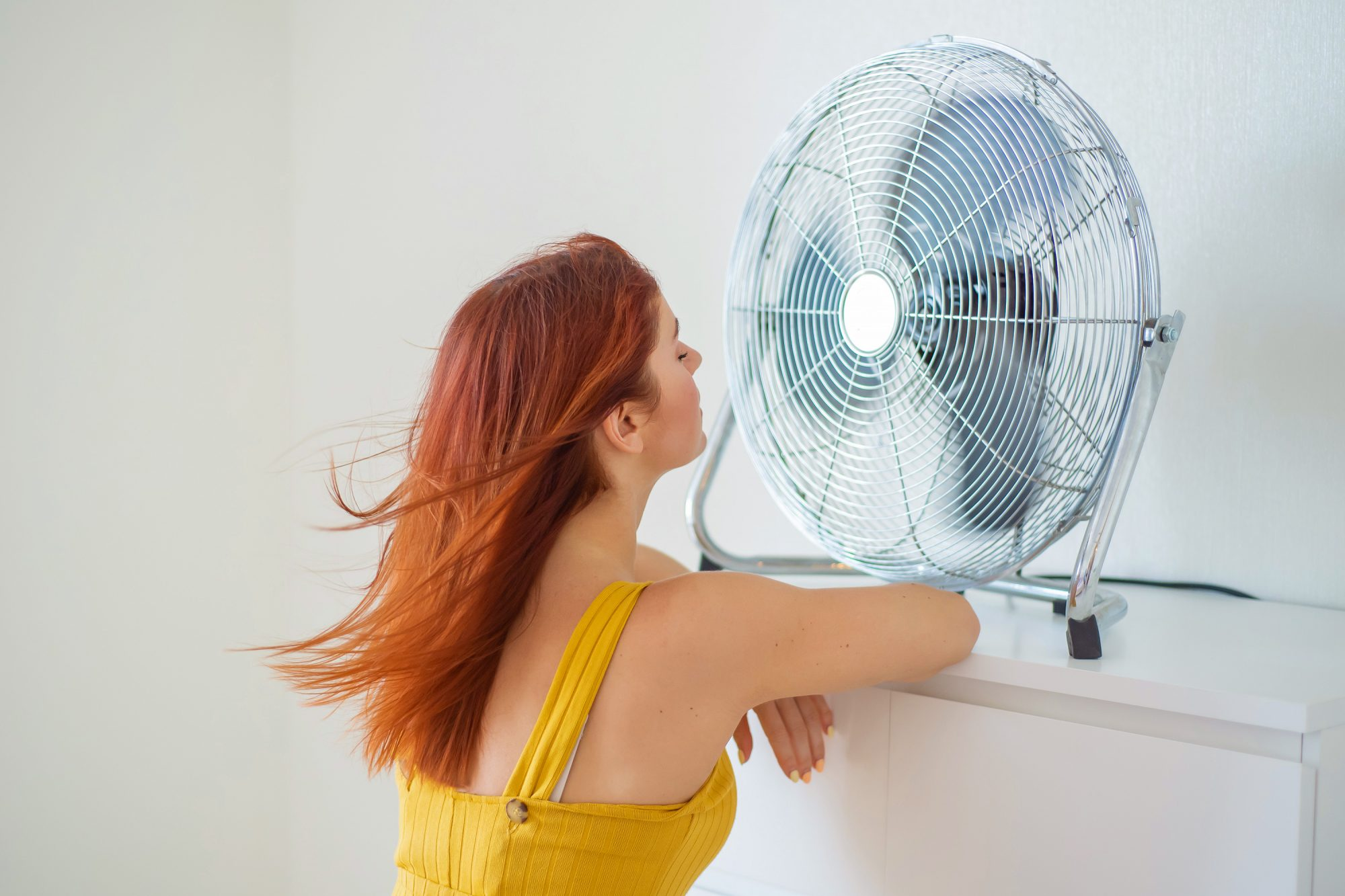 Woman in front of a fan on a hot summer day