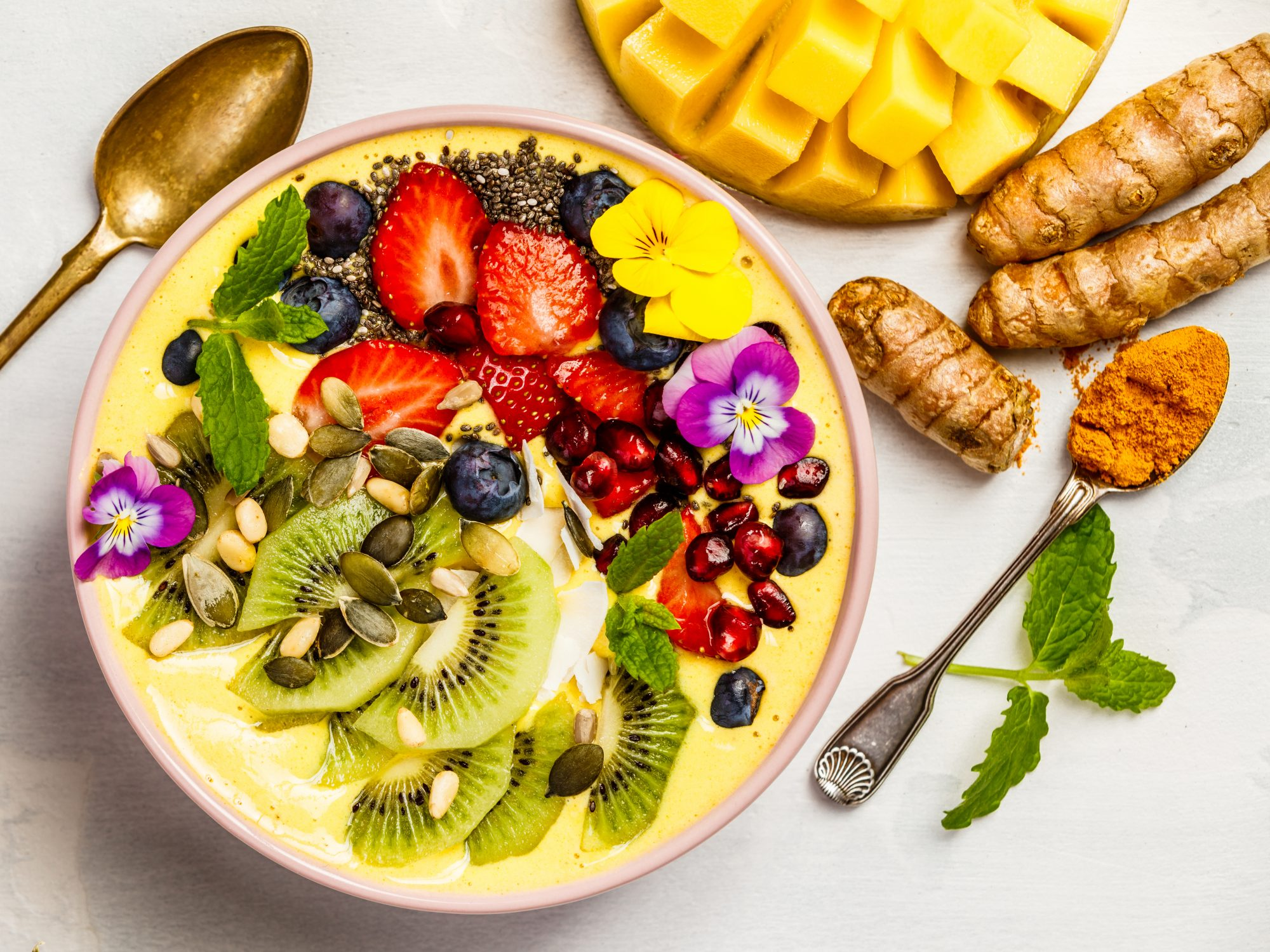 What Is an Anti-Inflammatory Diet?: Mango banana pineapple turmeric breakfast superfoods smoothie bowl topped with fruits, berries and seeds