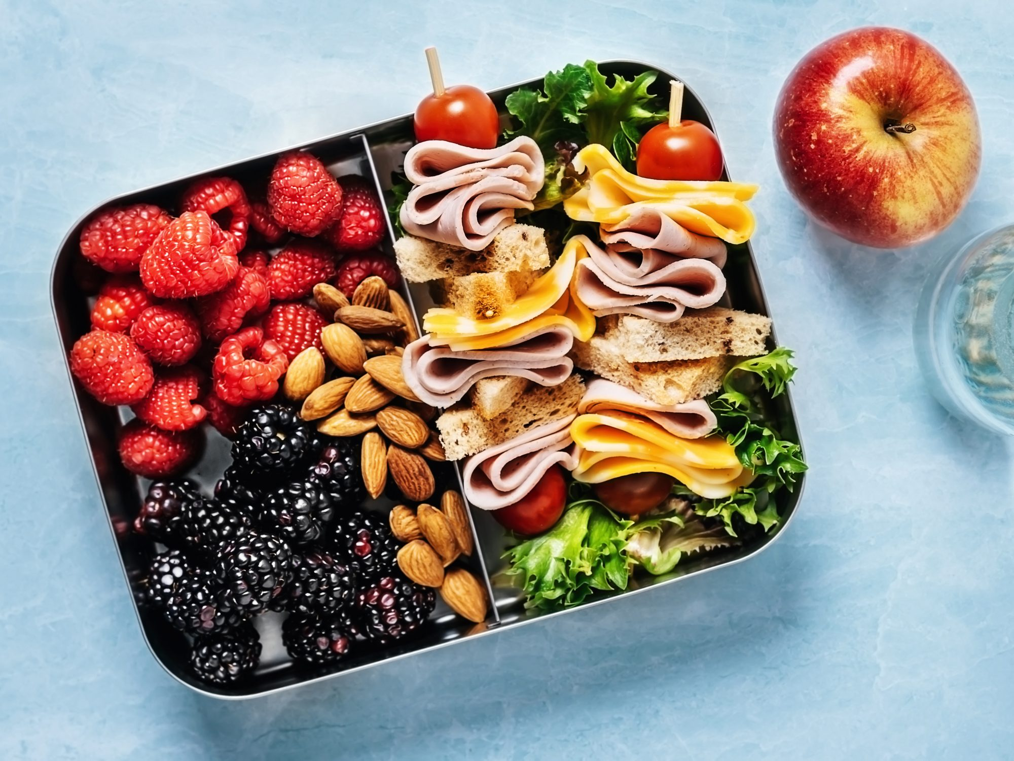 lunchbox filled with berries and a skewer style sandwich