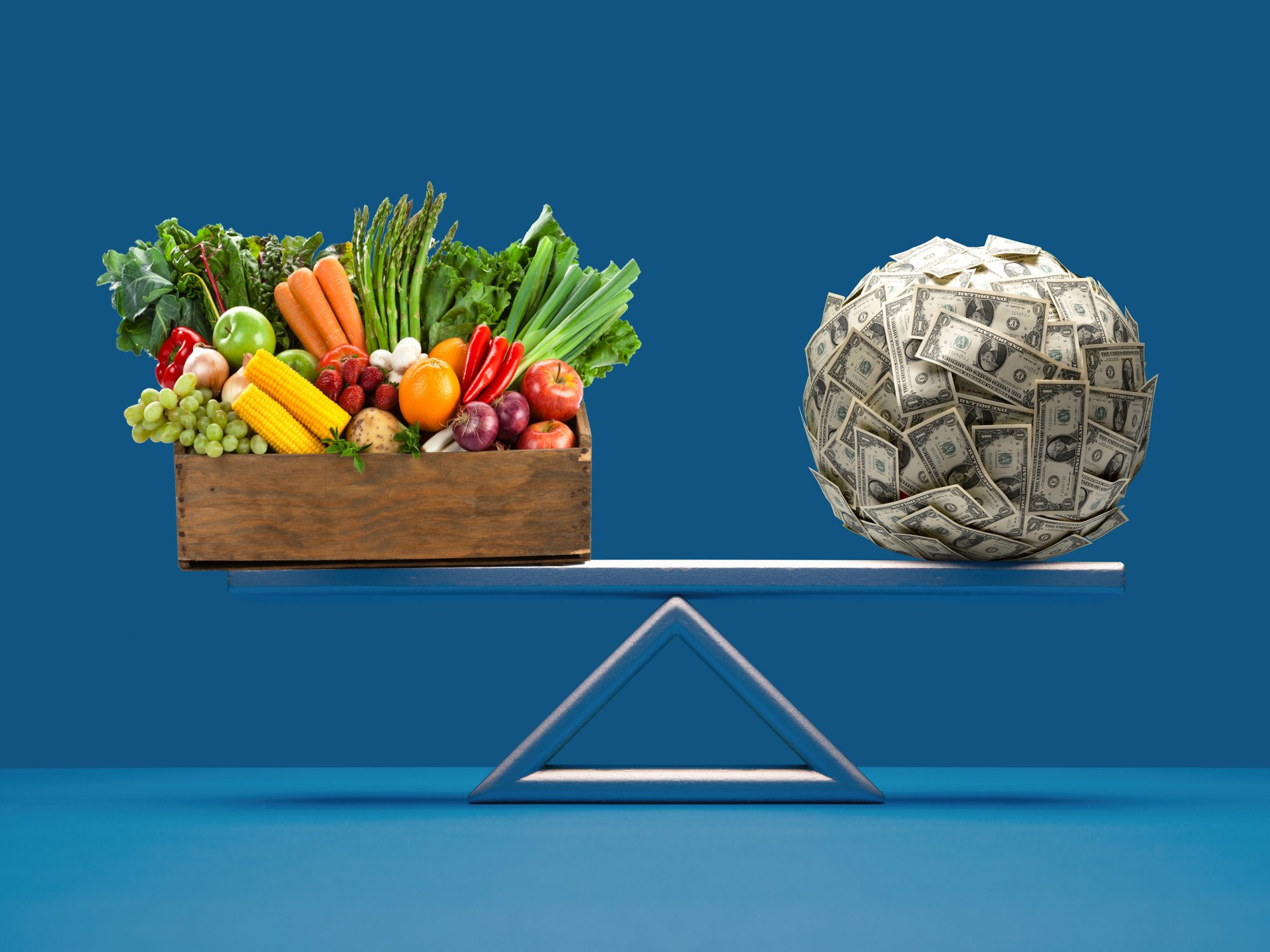 crate of vegetables and ball of US paper currency equally balanced on seesaw weight scale on blue surface and background