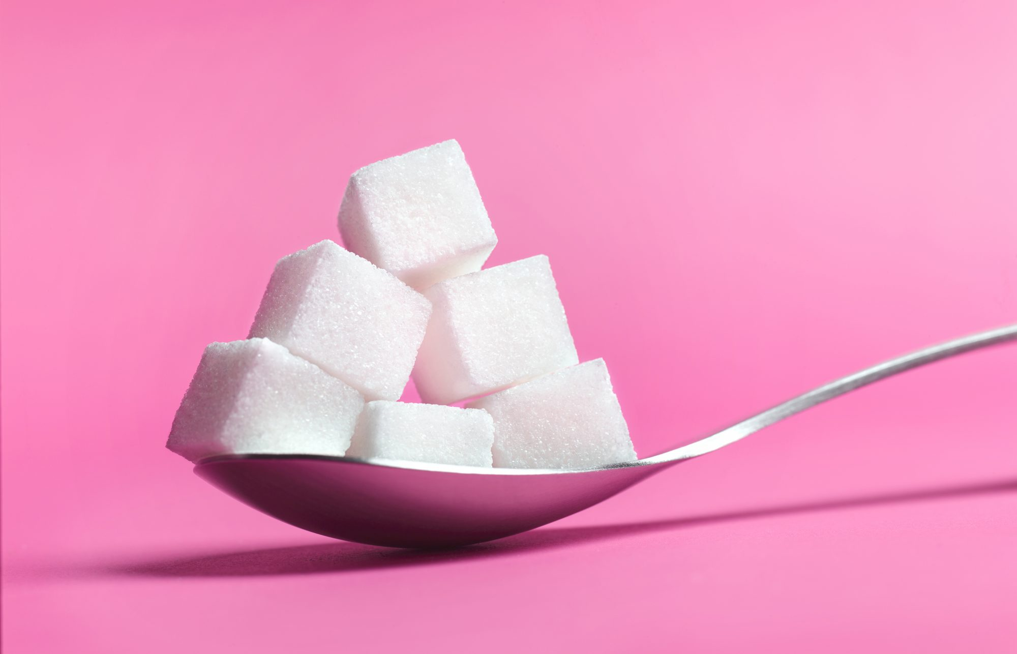 How Much Sugar Should You Eat Per Day? spoon with sugar cubes in it.