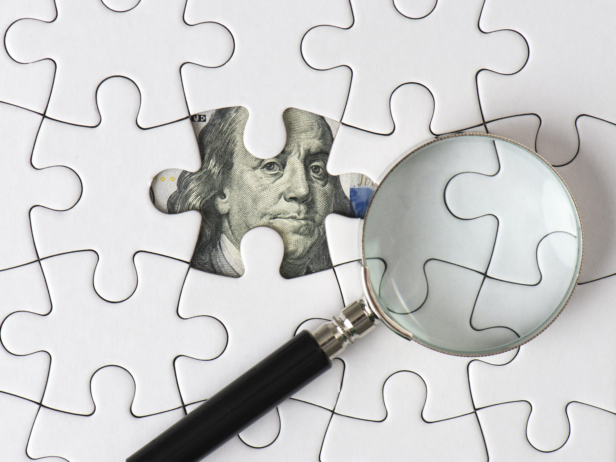 jigsaw puzzle with on piece missing and a dollar under it and a magnifying glass