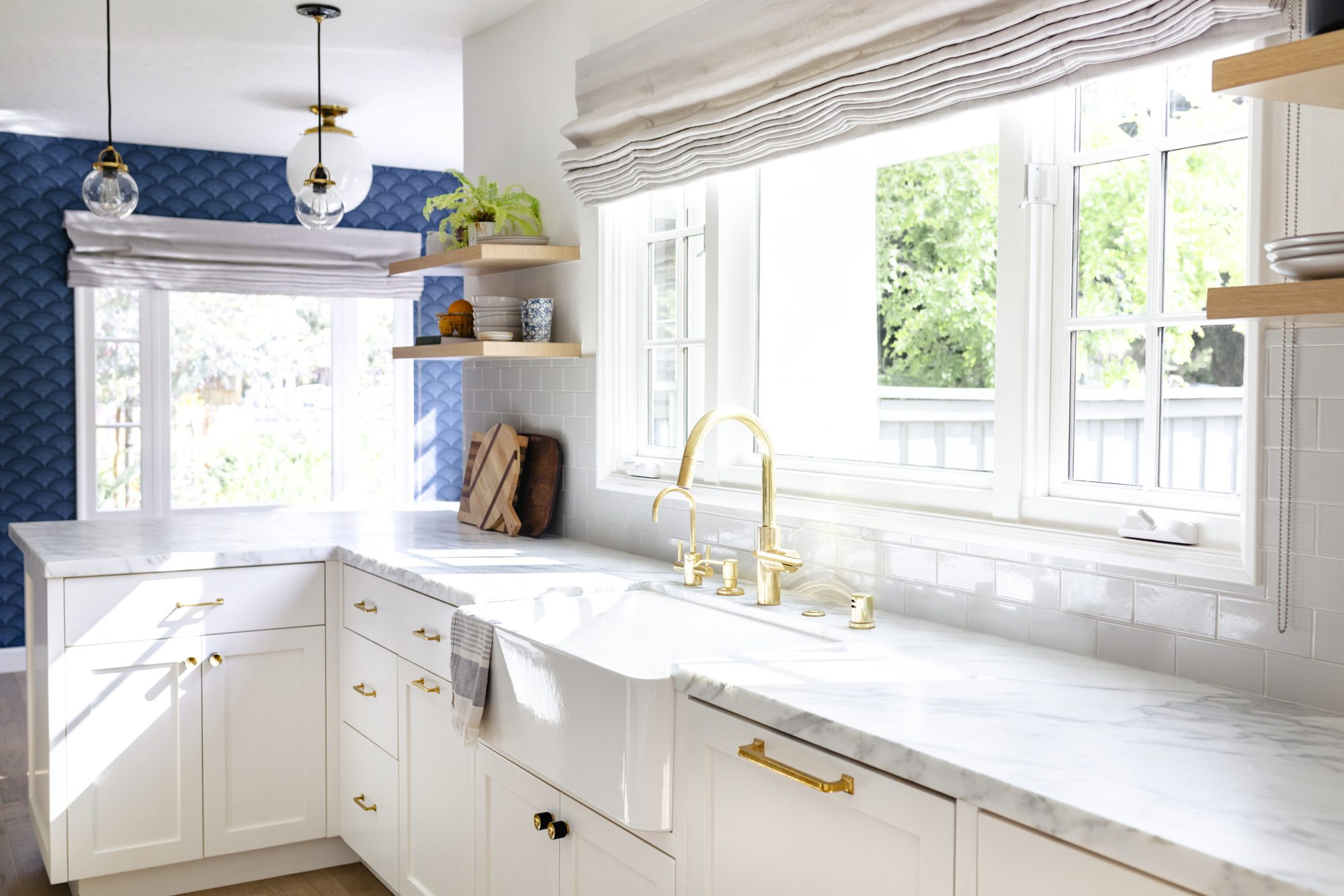 White kitchen with navy blue detailing and white marble counter with gold fixtures.