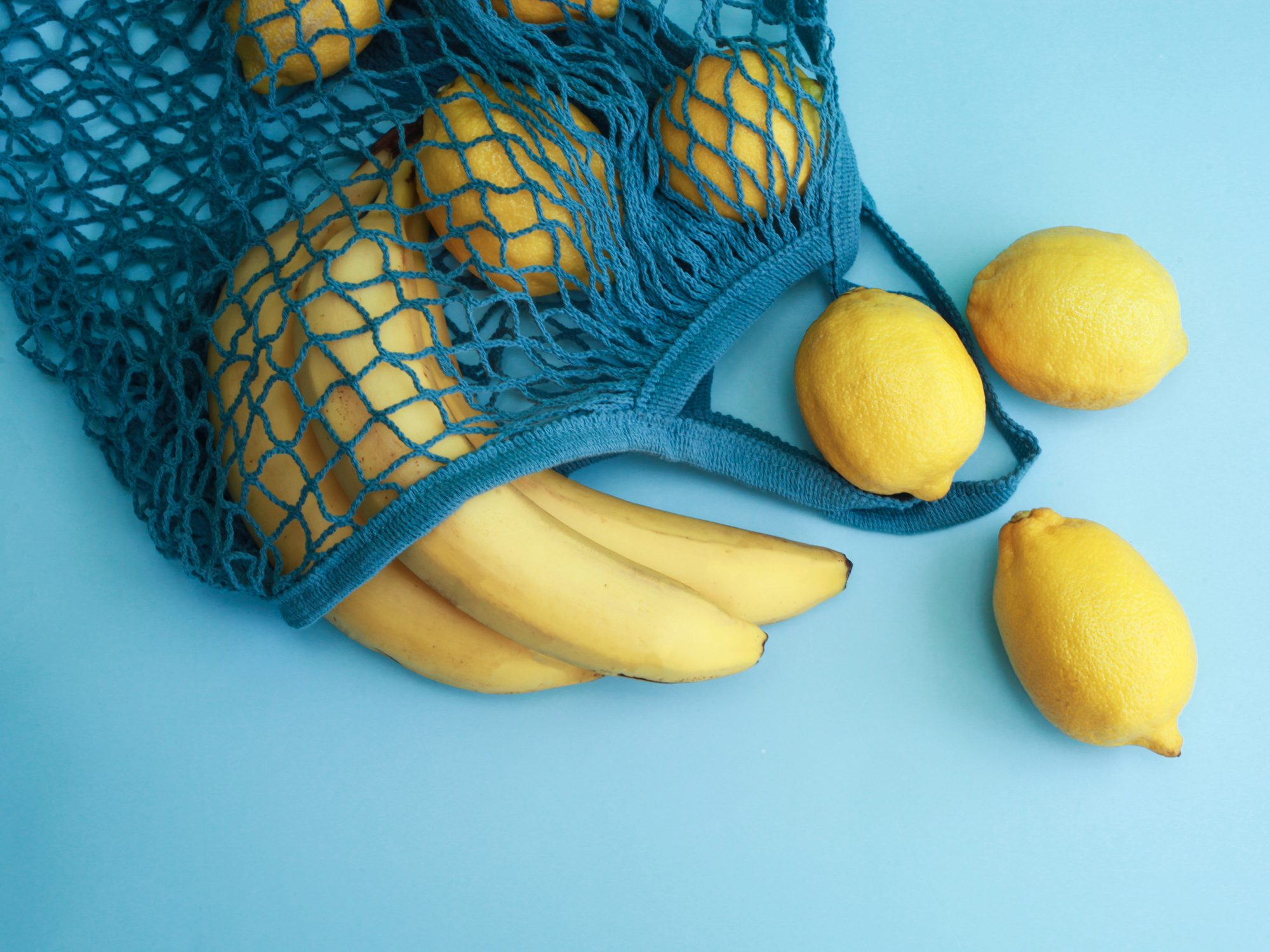 Lemon yellow fruits in blue mesh bag over blue background with copy space
