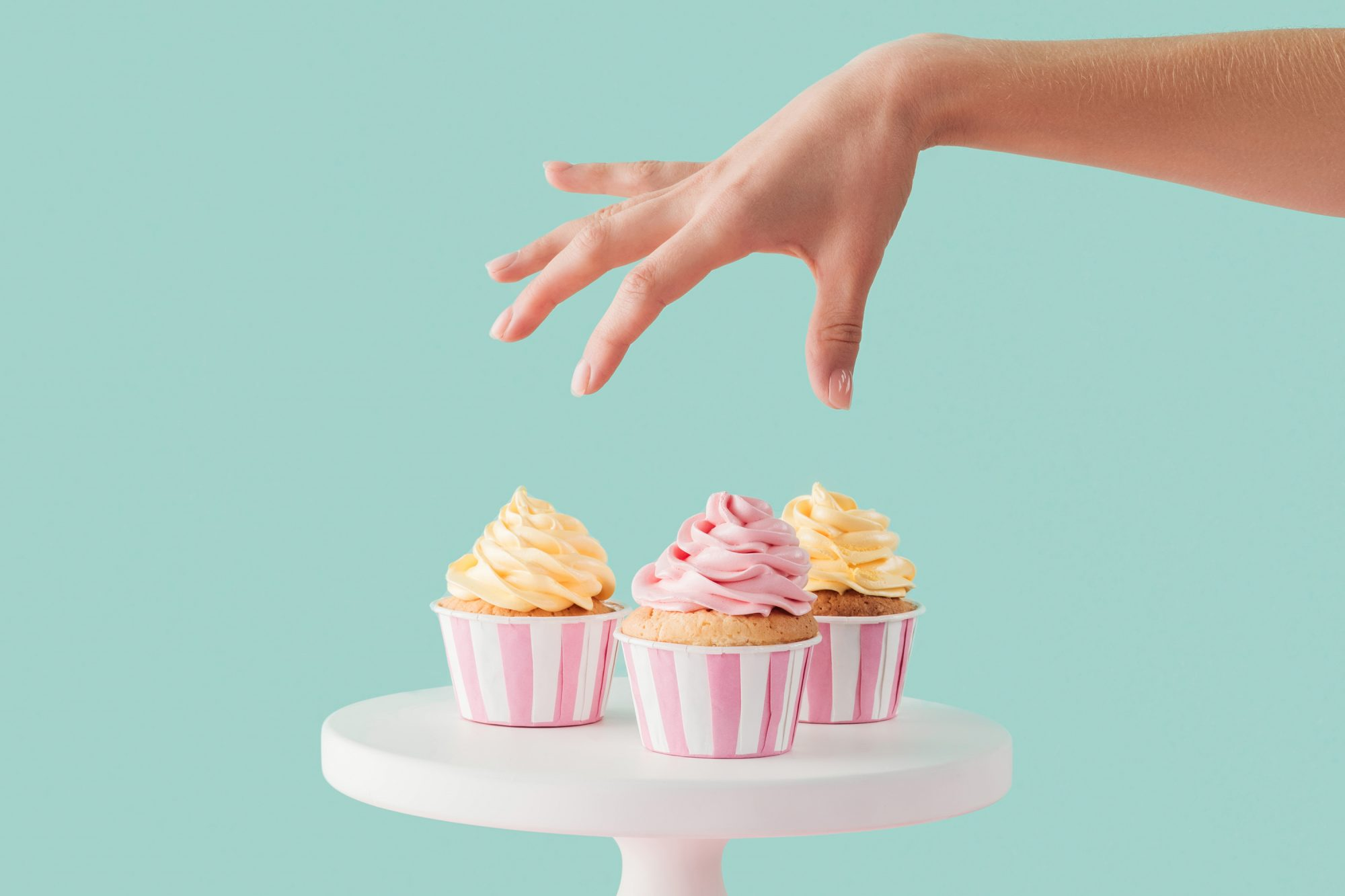 how-to-stop-sugar-cravings: woman reaching for cupcakes