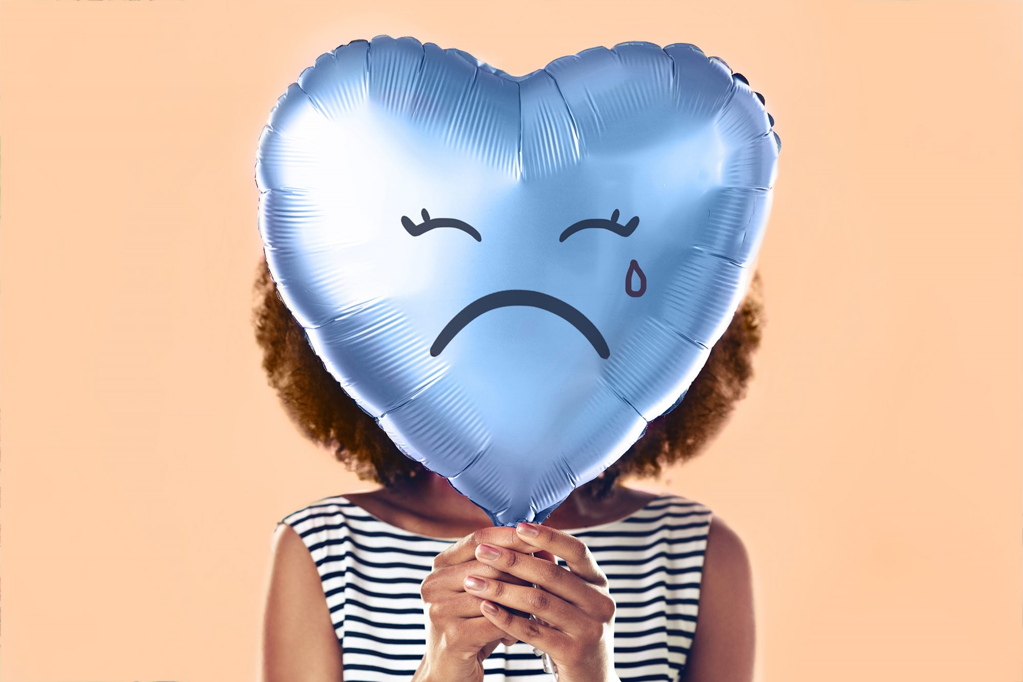 Healthy Benefits of Crying: woman holding balloon with frowny face