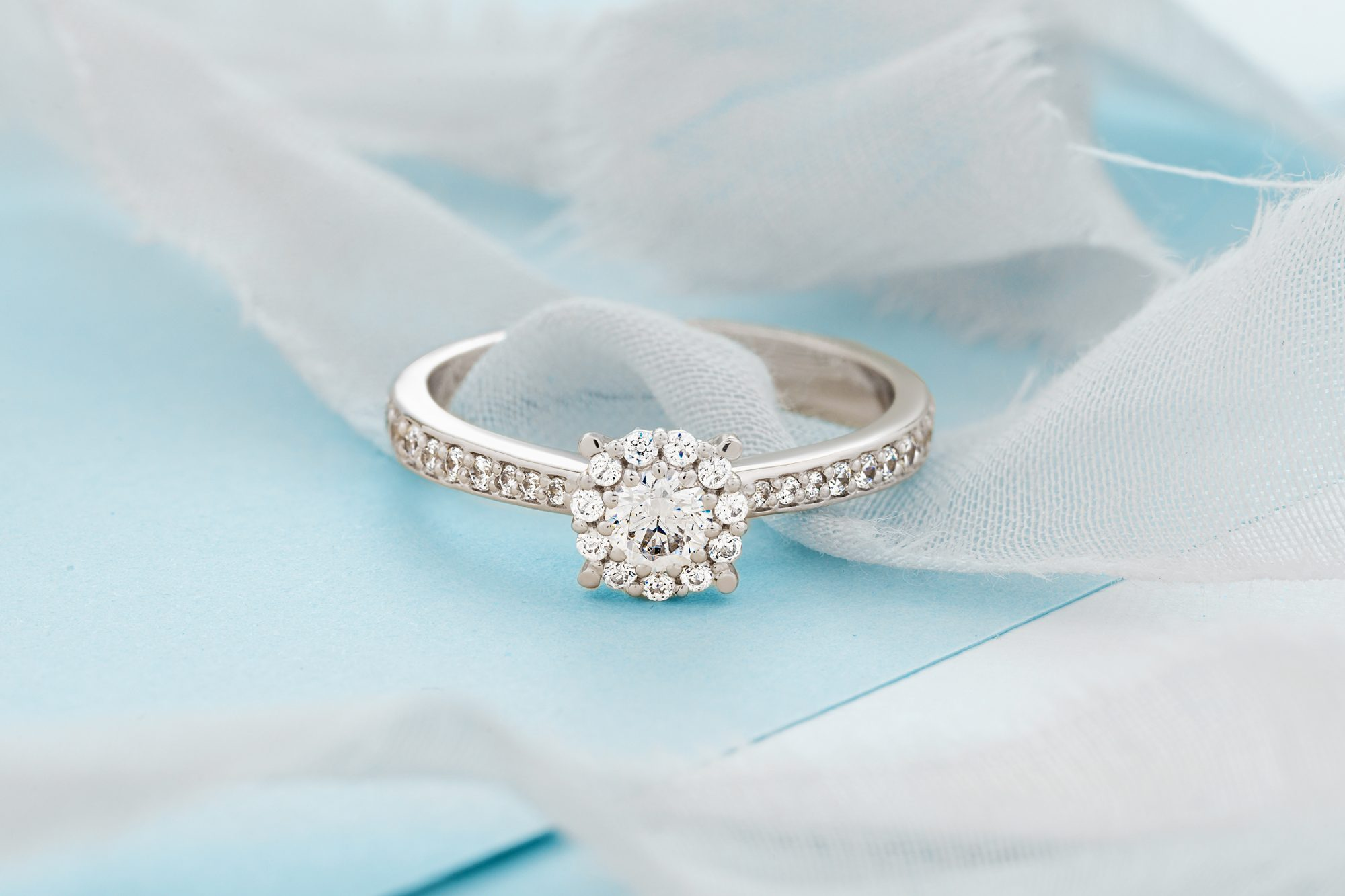 Most Searched Engagement Ring Styles from Google: halo engagement ring on blue background with ribbon