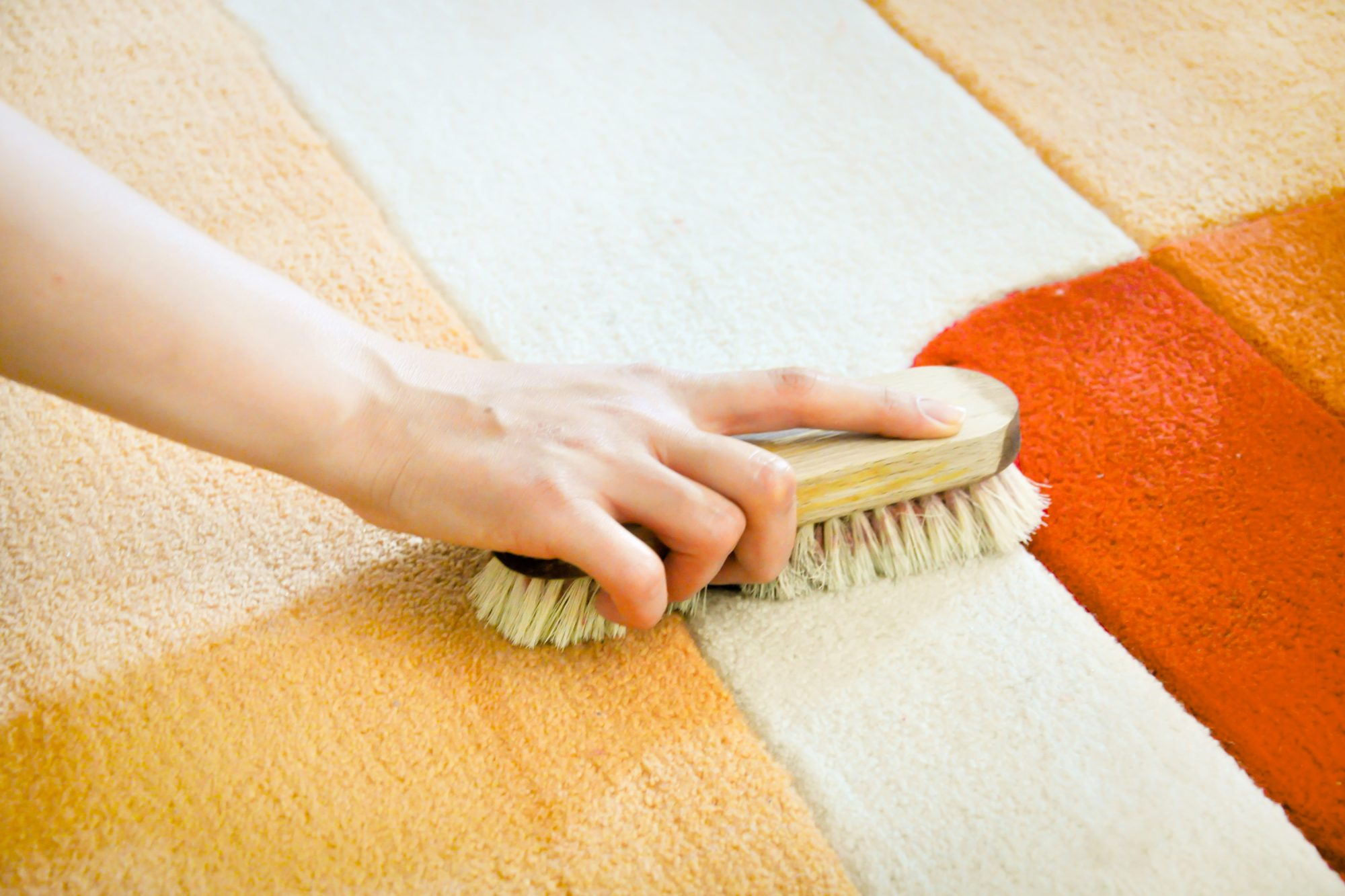 hand scrubbing carpet stain with cleaning solution
