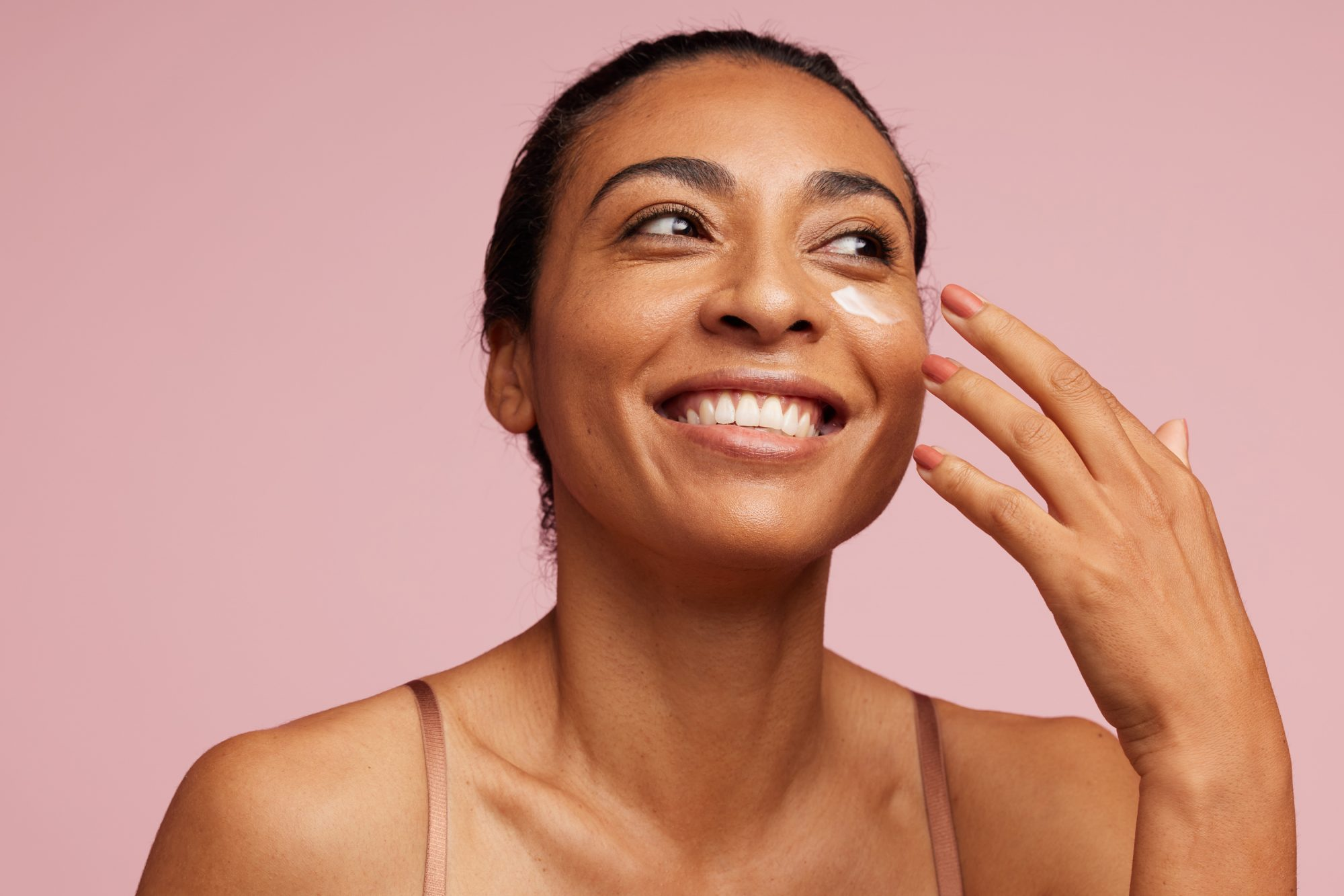 woman with clear and healthy skin applying skin cream