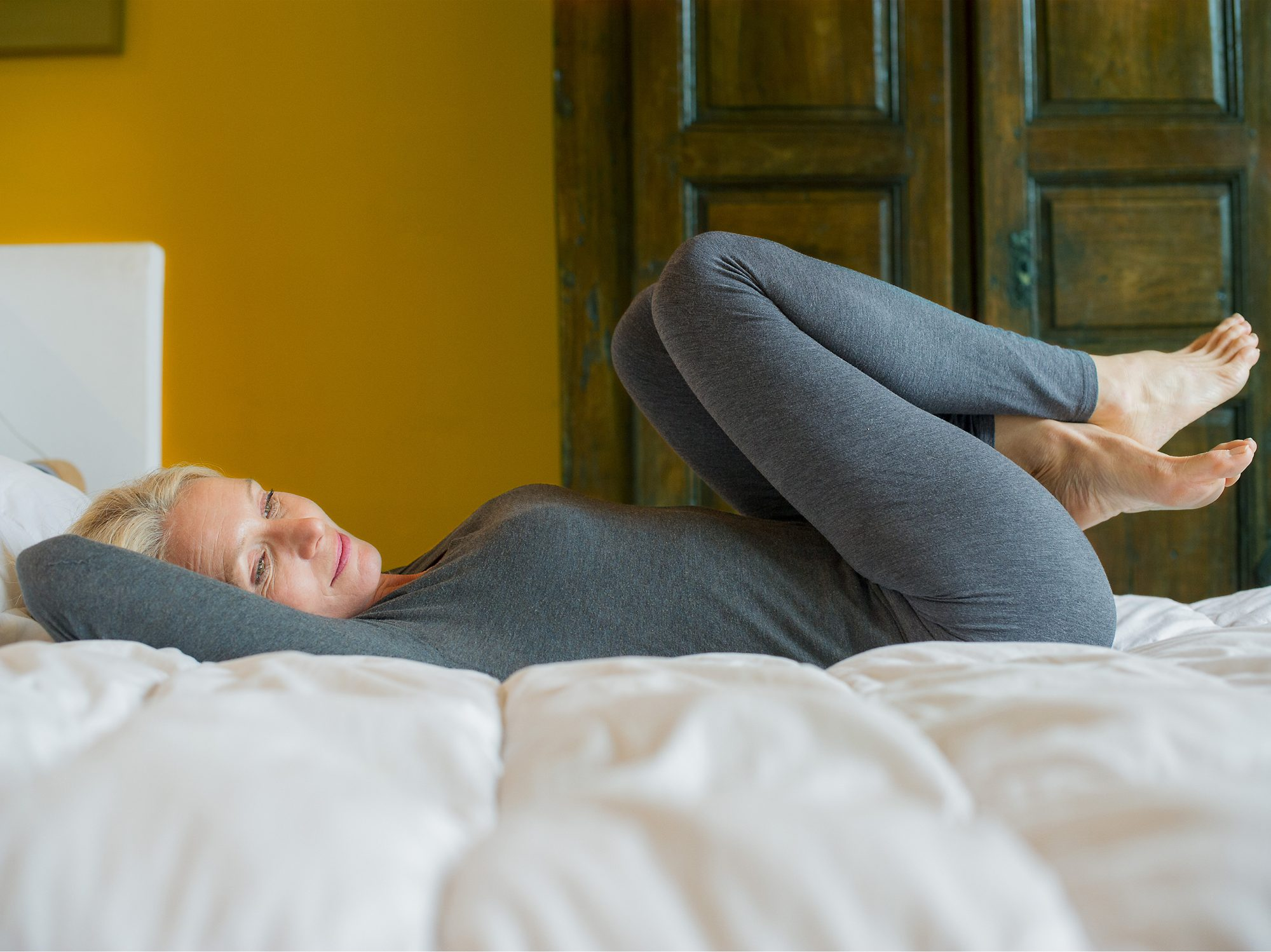 7 Calming Yoga Stretches You Can Do From Your Bed