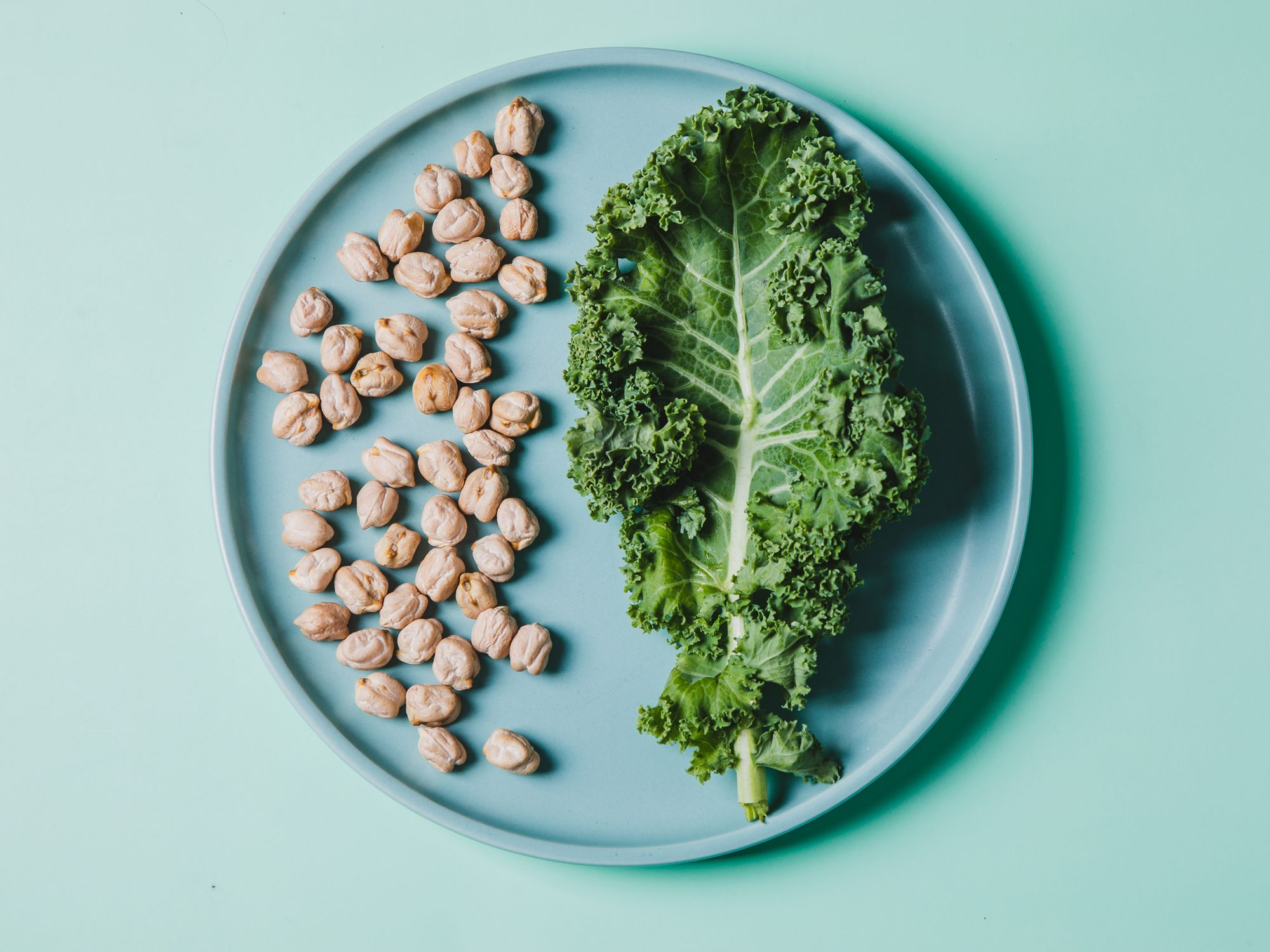 overhead view of super food kale and chickpeas in a plate against green background: healthy sources of fiber