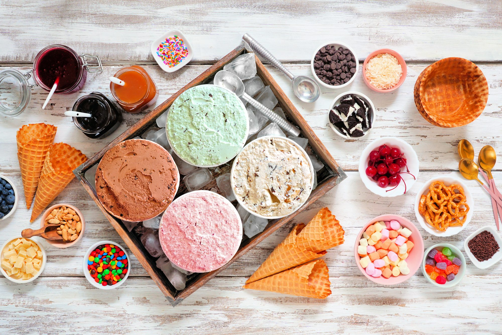 ice cream bar top view table scene on a rustic white wood background