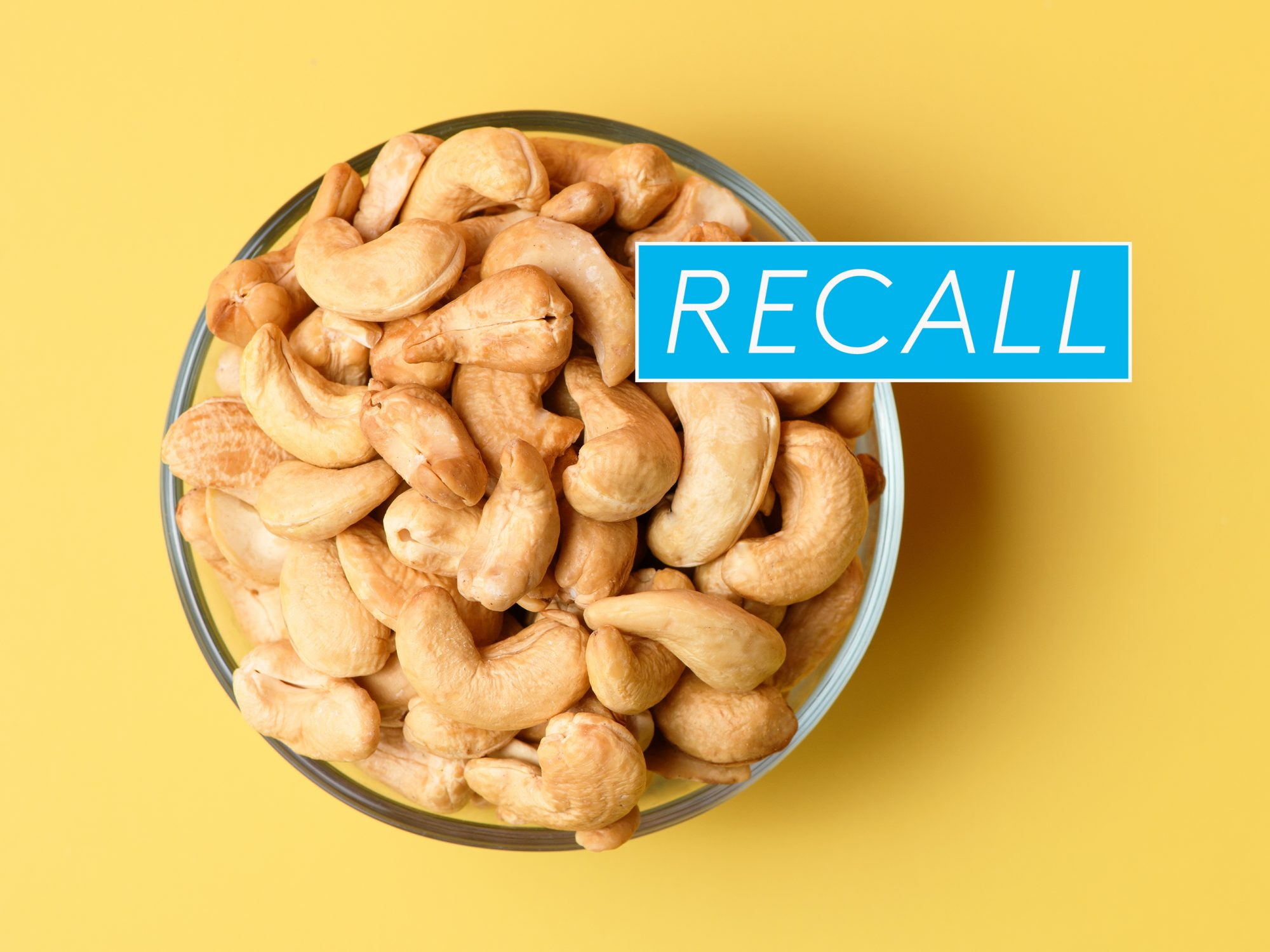 Flat lay of cashew in glass bowl with a recall sign on it