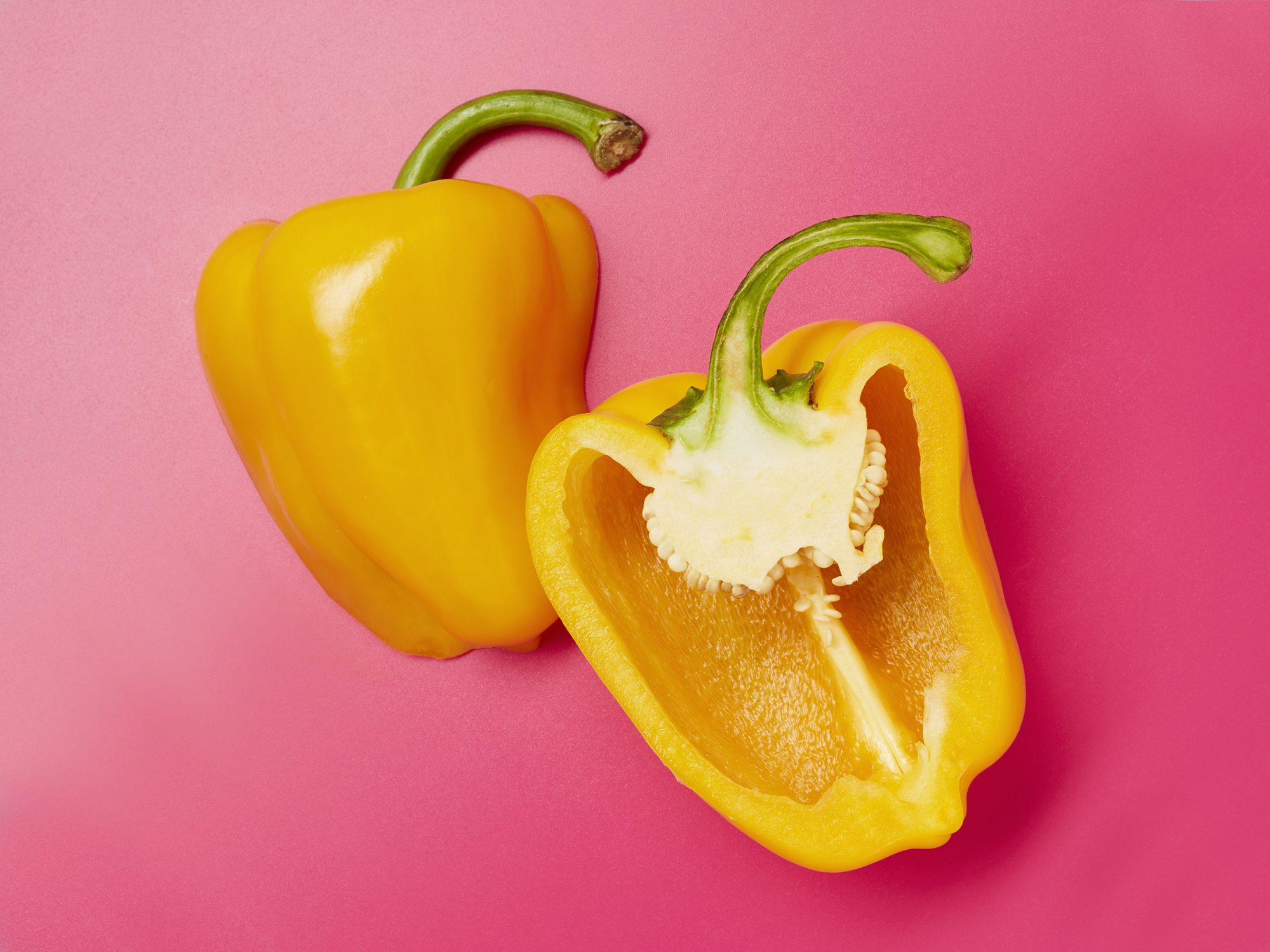 Still life of sliced yellow bell peppers on pink background