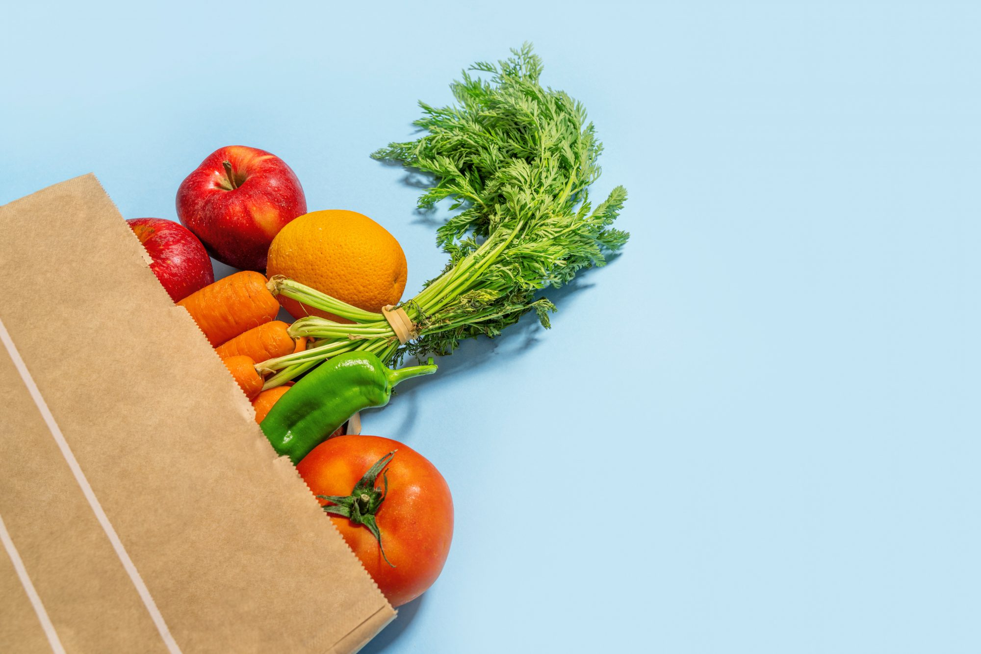 Grocery back of vegetables on a blue background