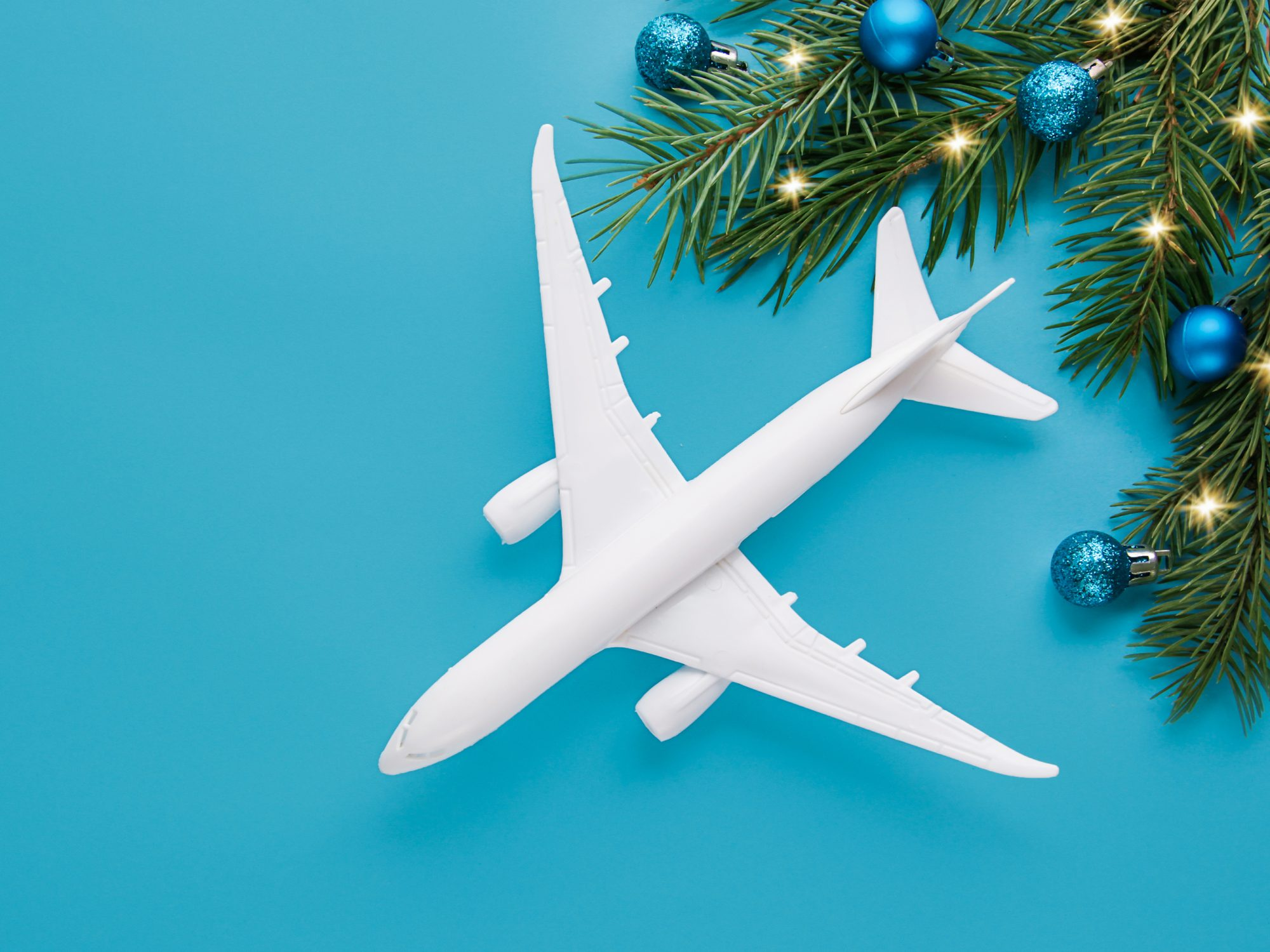 Christmas travel planning. Traveling as gift. White blank model of passenger plane and gift box on background. Top view or flat lay.