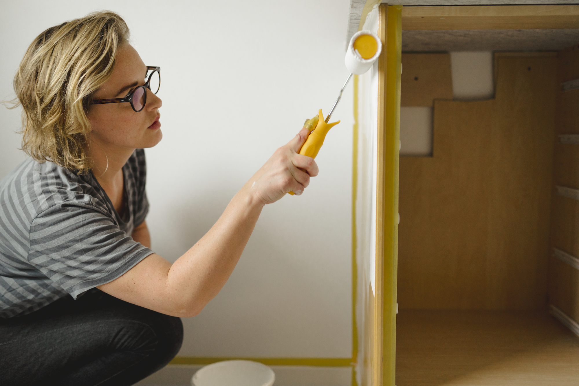 Woman Painting Kitchen Cabinets White