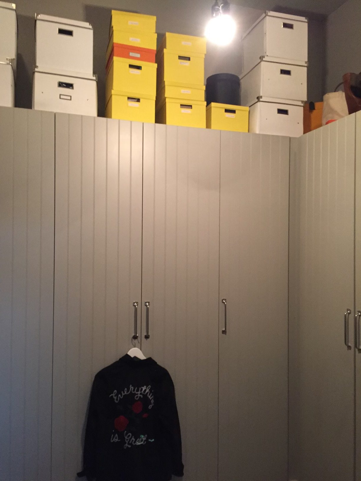 dim closet with doors and boxes on top