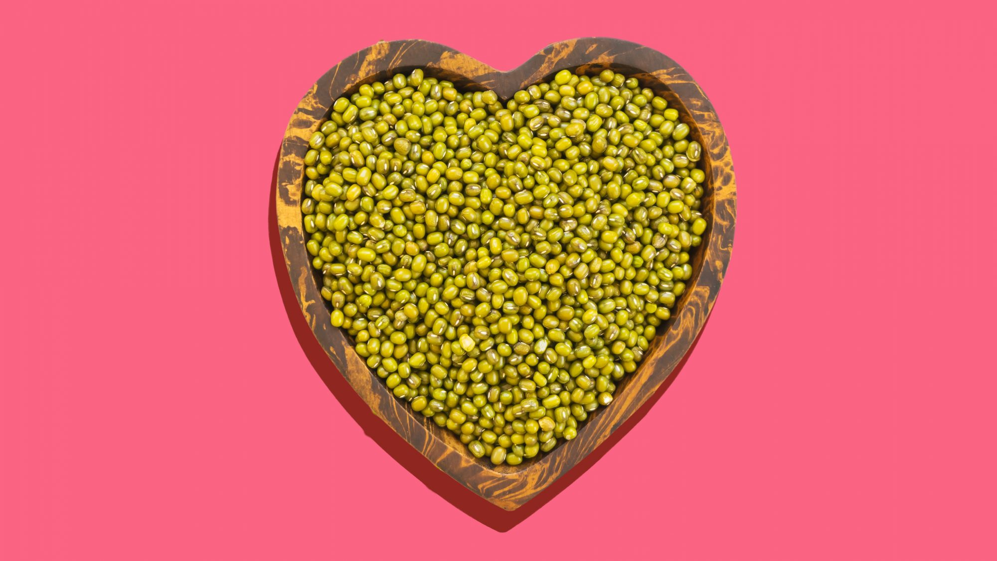 Directly Above Shot Of Mung Beans In Heart Shape Bowl Over White Background